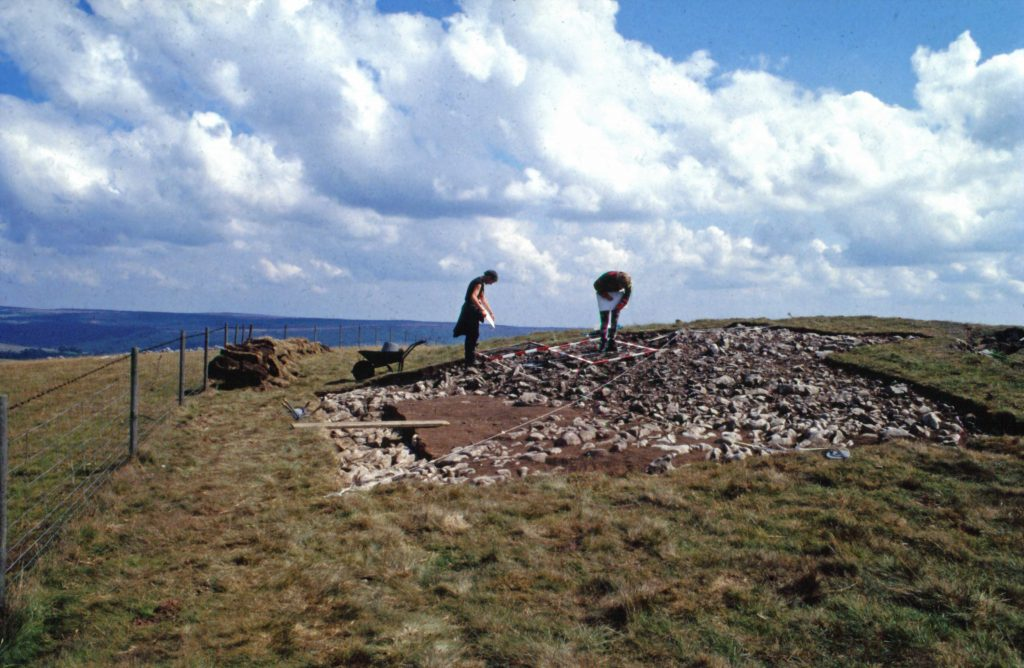 A photo of an archaeological dig on a green hillside under a blue sky. Two people are inspecting a dig site.