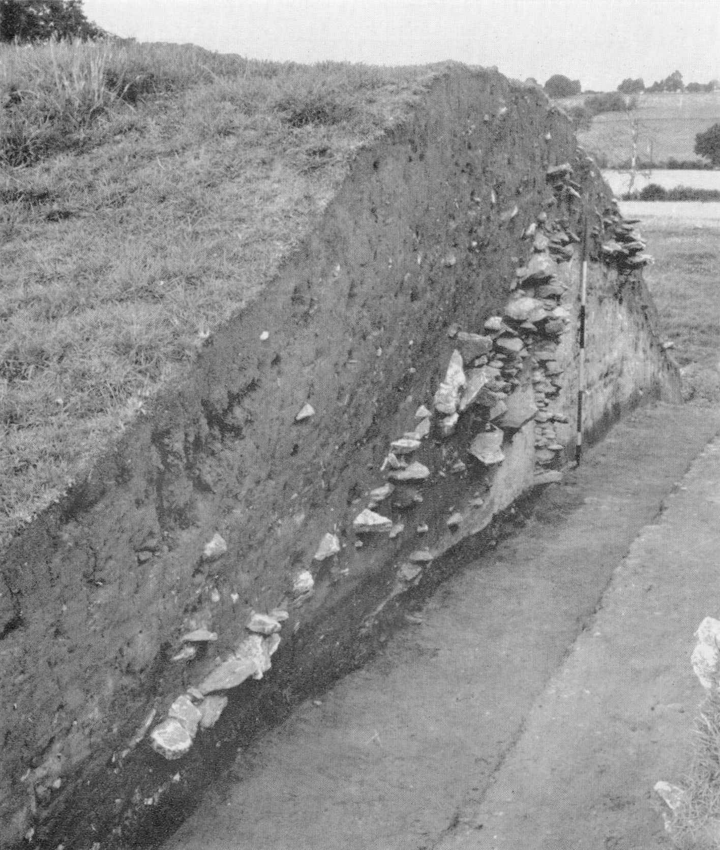 A photograph of a grassy mound which has been cut into to reveal a layer of stones underneath the surface.