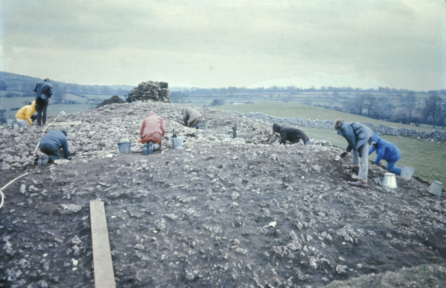 A photo of several people working on a shallow archaeological excavation. Grass has been removed, exposing a stony surface just below the ground.