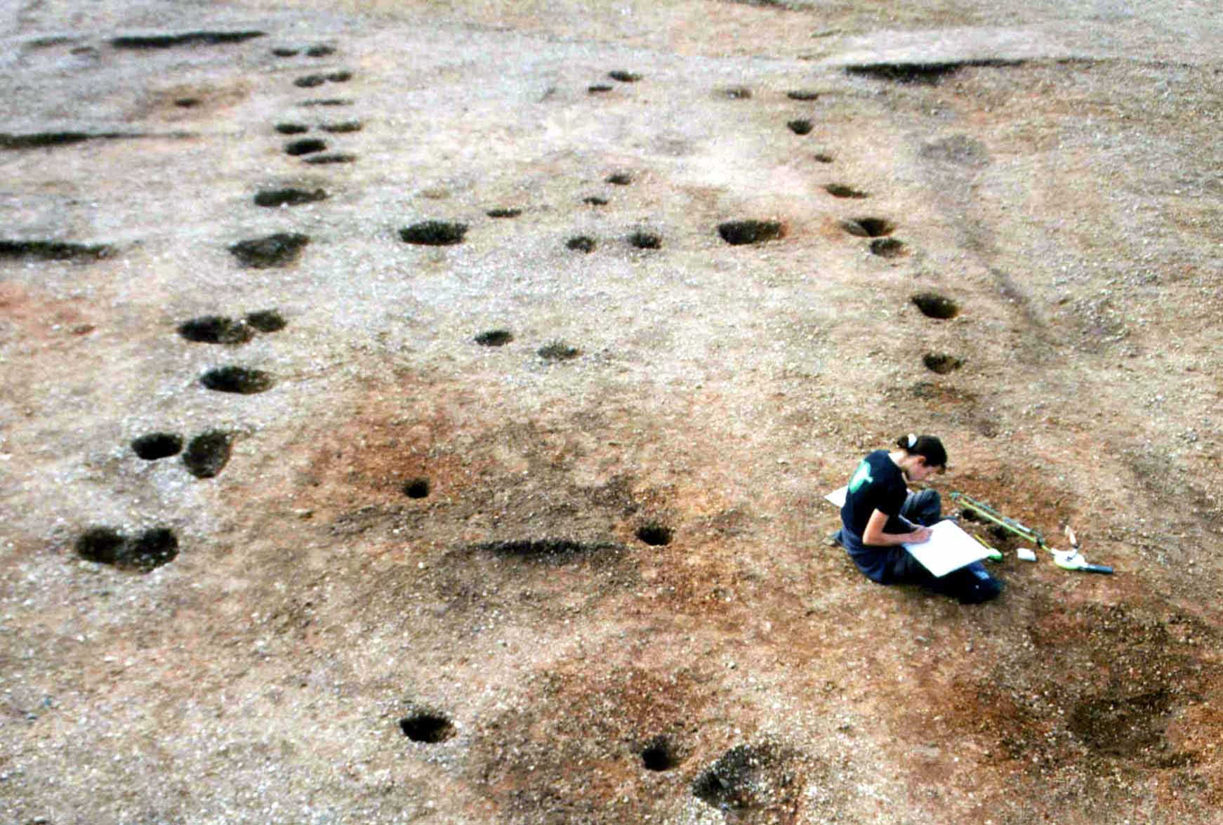 A photograph of a person sitting on a smooth earthen surface, in which a series of regular holes show the outline of a building.