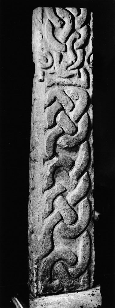 A photo of a stone pillar, on which intricate carved knotwork can be seen.