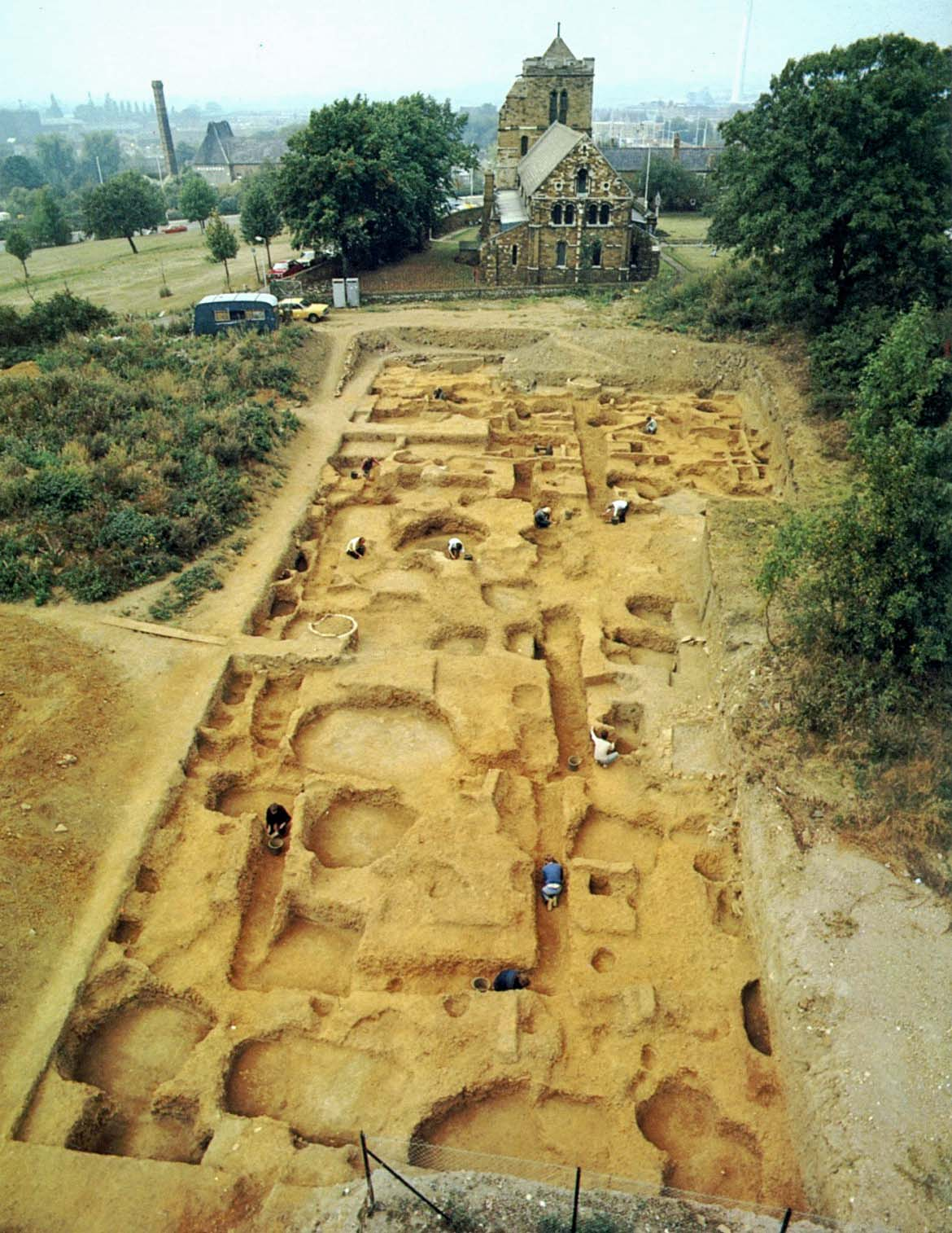 A photo of a very large archaeological excavation approximately 100 metres long, exposing an intricate and complex structure just underneath the surface. A church can be seen just behind the excavation.