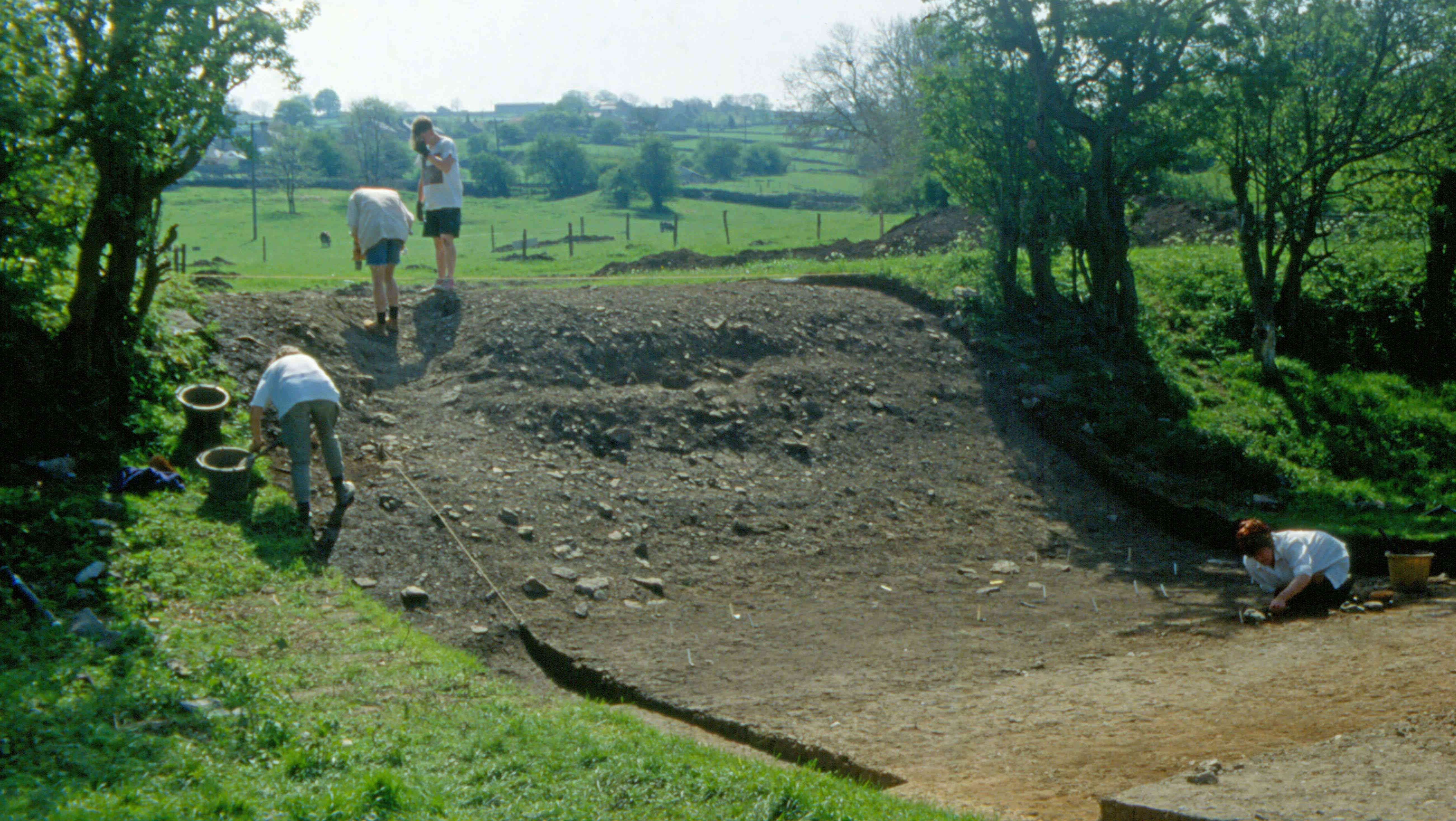 A photo of four people excavating a grassy bank, revealing stony debris.