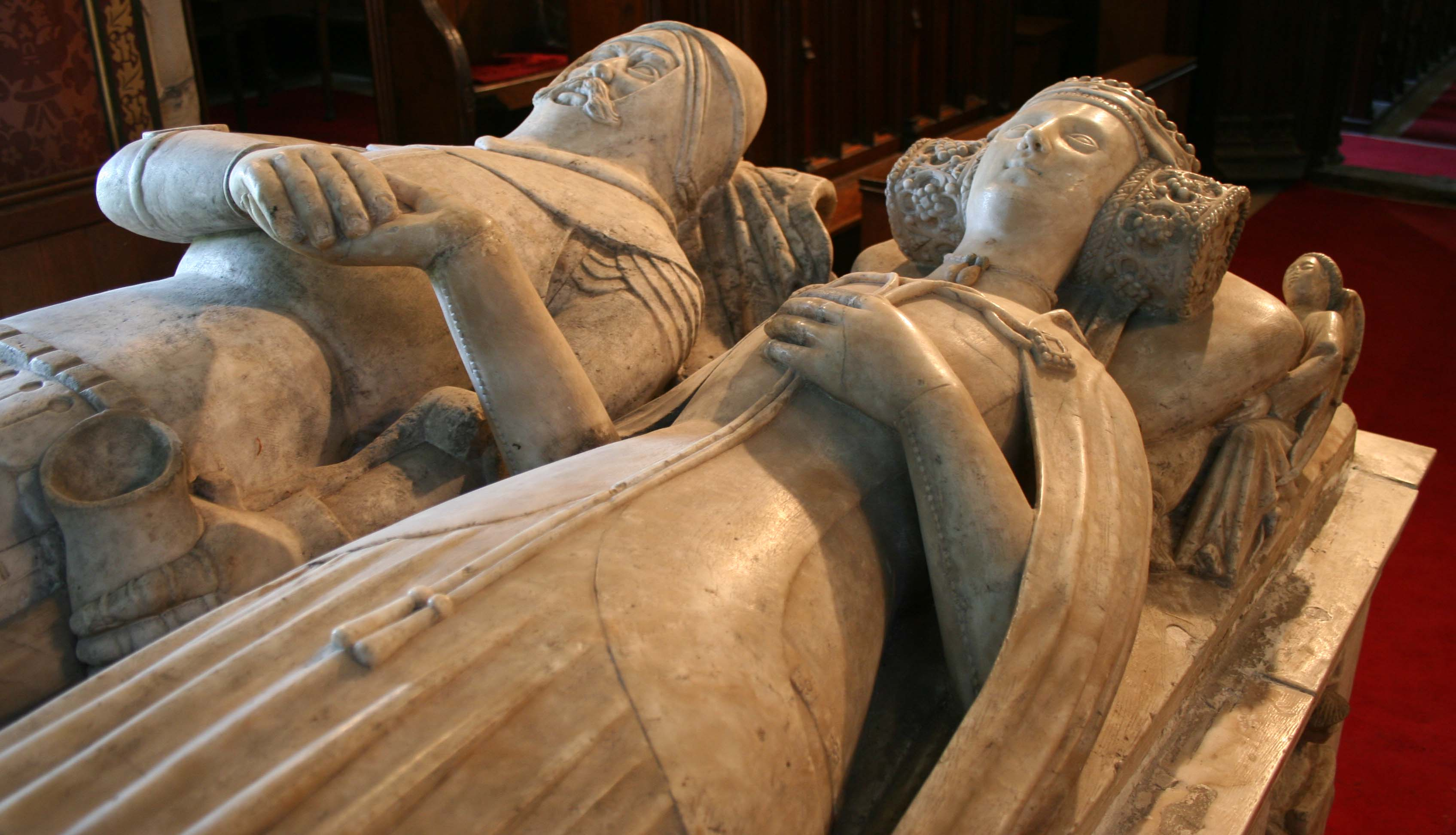 A photo of two a man and a woman carved out of stone. The man is wearing armour and the woman is wearing a dress and cloak. The figures are lying on their backs, and are holding hands.