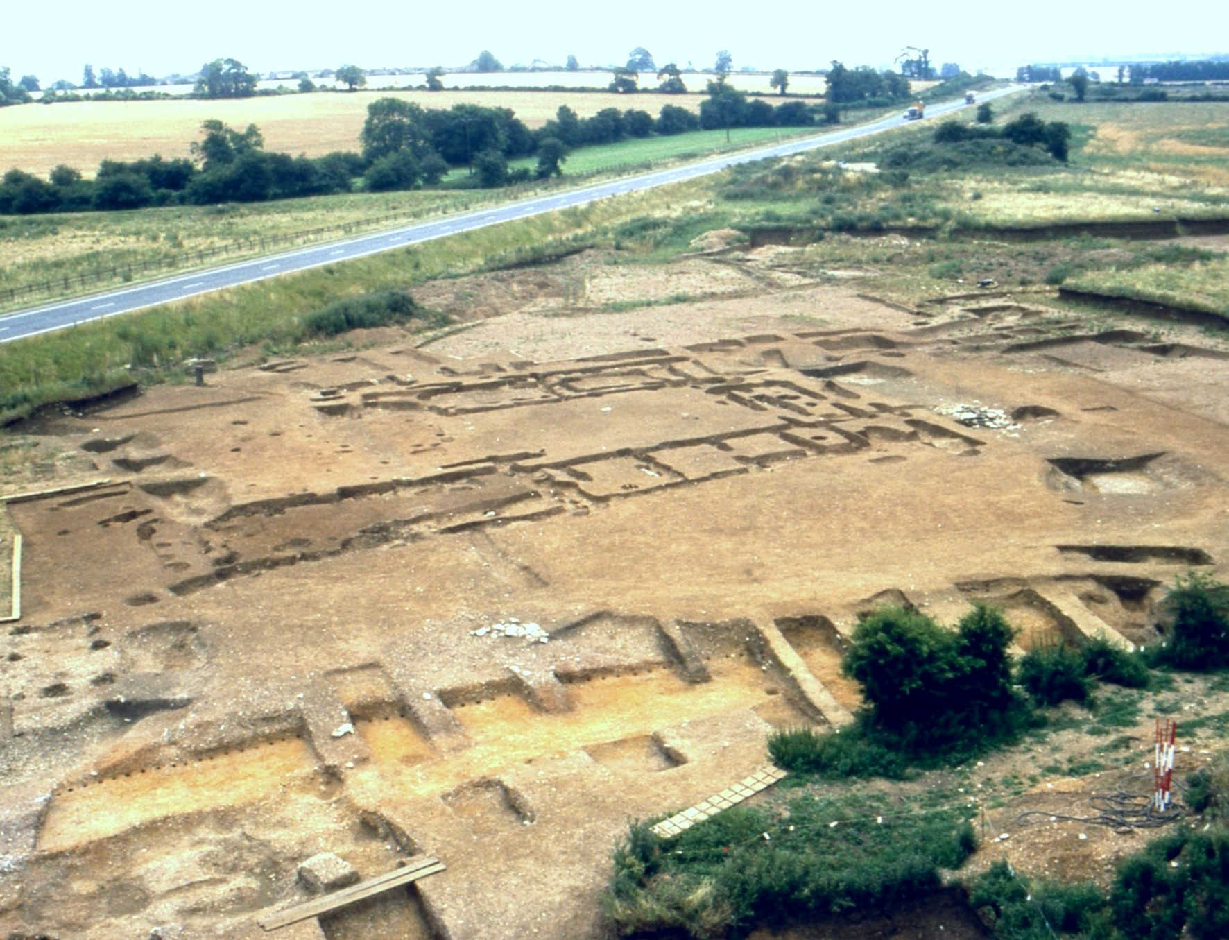 A photograph of a very large archaeological excavation, showing large and complex rectilinear structures following the floorplan of a large building.