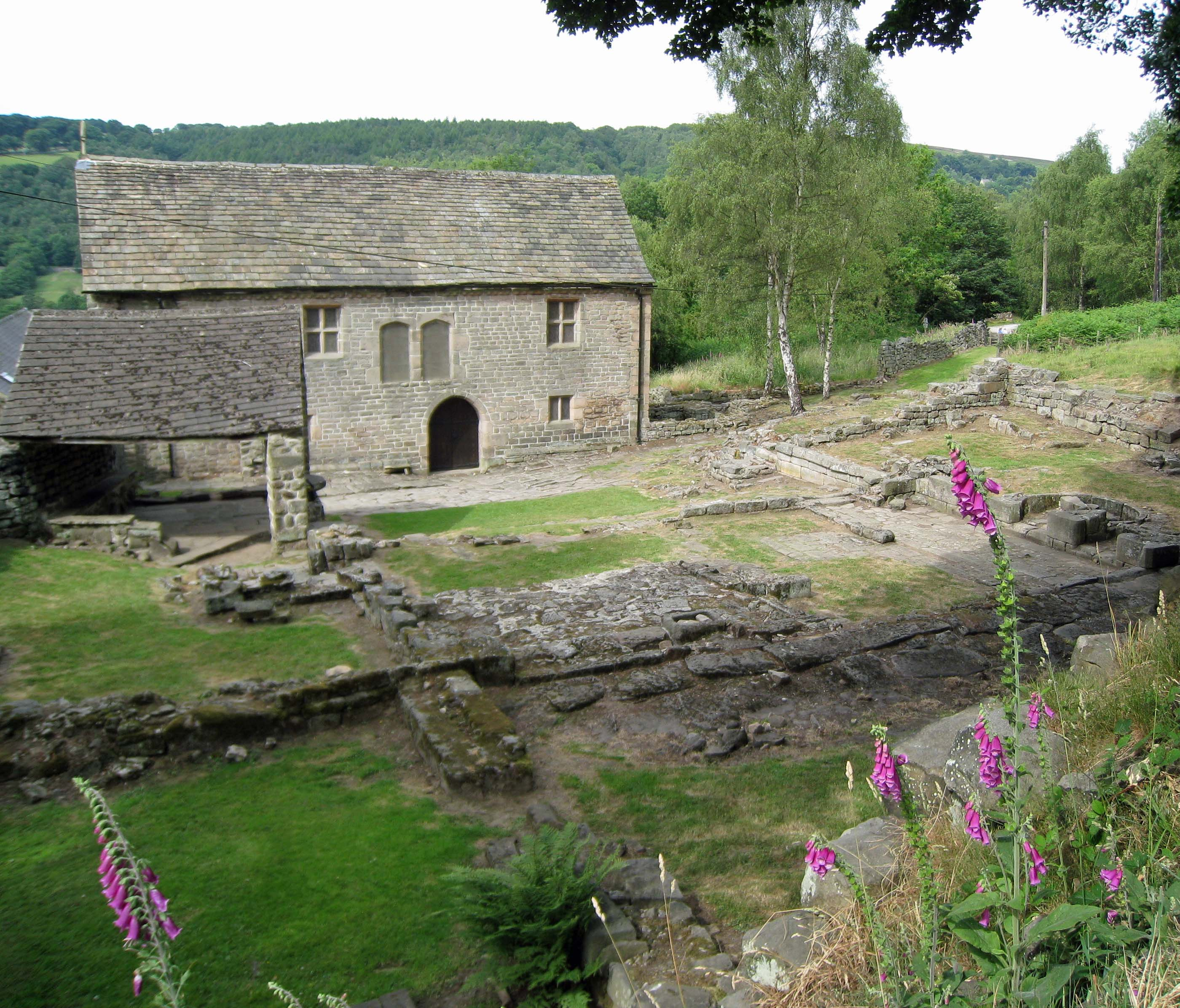 A photograph of stone ruins on a wooded hillside. Behind the ruins is an intact, two story, stone building with rectangular windows and an arched doorway.