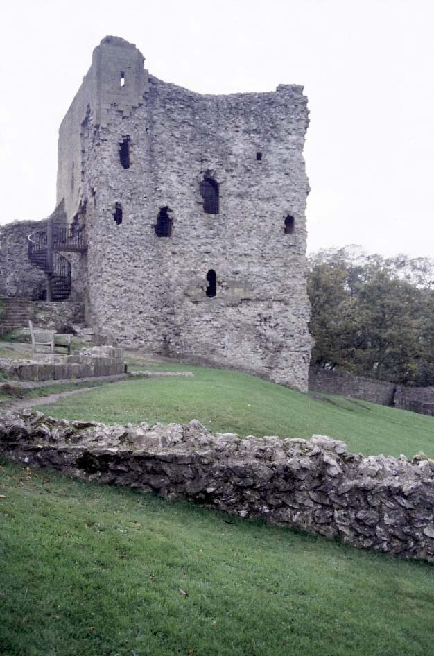 A photograph of a partly ruined stone tower on a grassy hillside. The outer surface of the tower is missing, and the material inside of the wall can be seen. Surrounding the tower can be seen stone walls, also partially ruined.