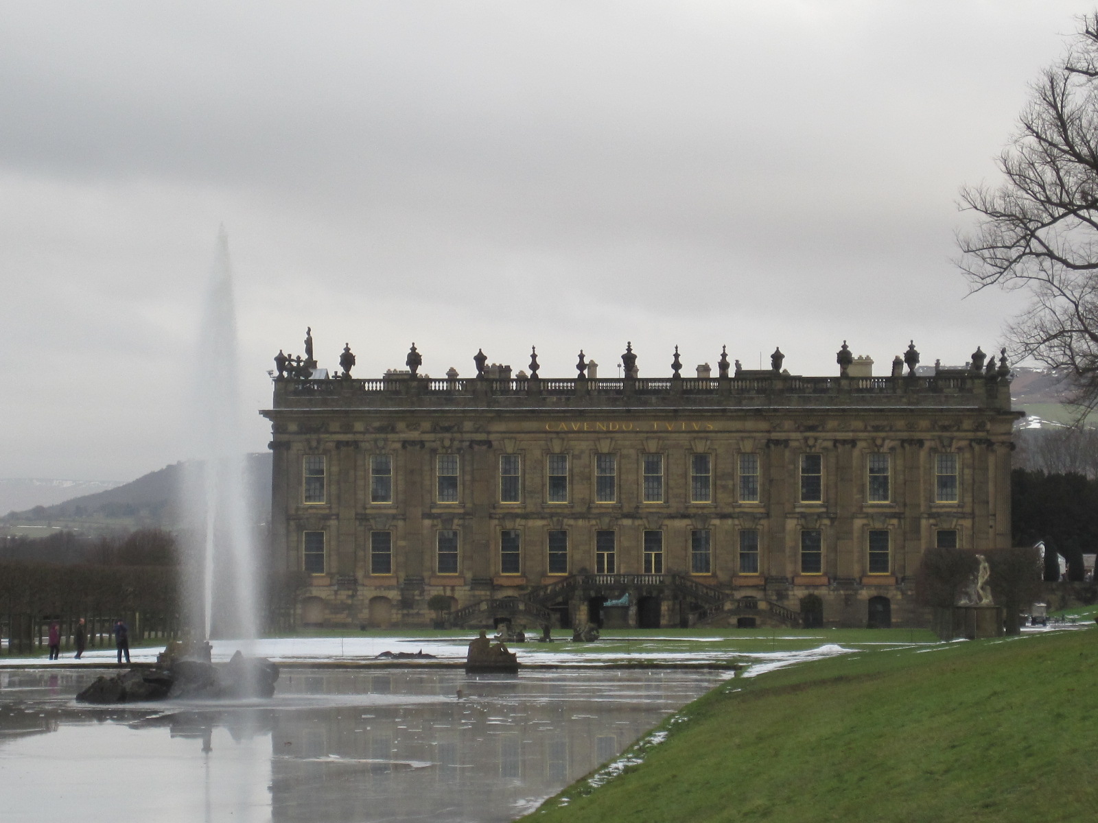 A photograph of a large manor house. In the foreground is a lake with a large vertical fountain. The house has a flat roof, three storys and 12 bays. The roof is covered with ornamentation.