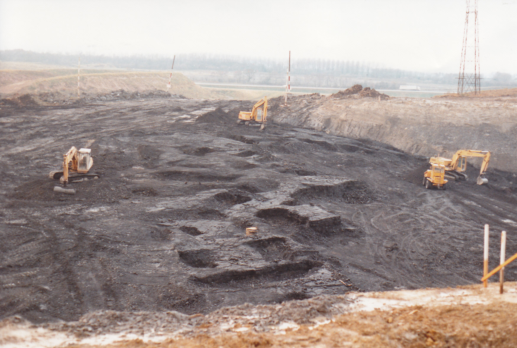 A photo of an open cast mine being excavated by diggers and trucks. In the center can be seen a series of passages and spaces which have been exposed by the digging.