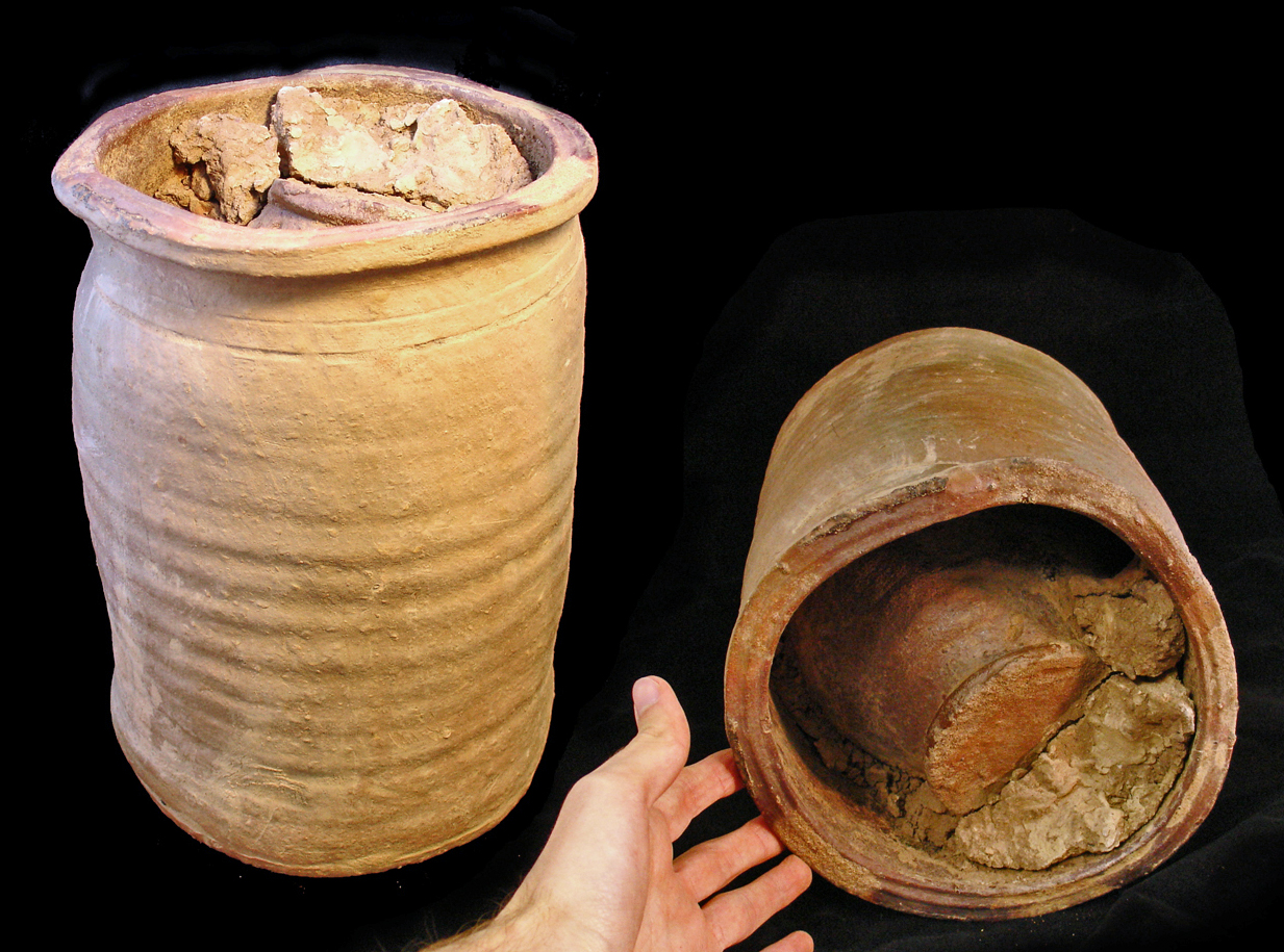 A photograph of a roughly cylindrical pot, inside of which can be seen a smaller object, packed in with debris.