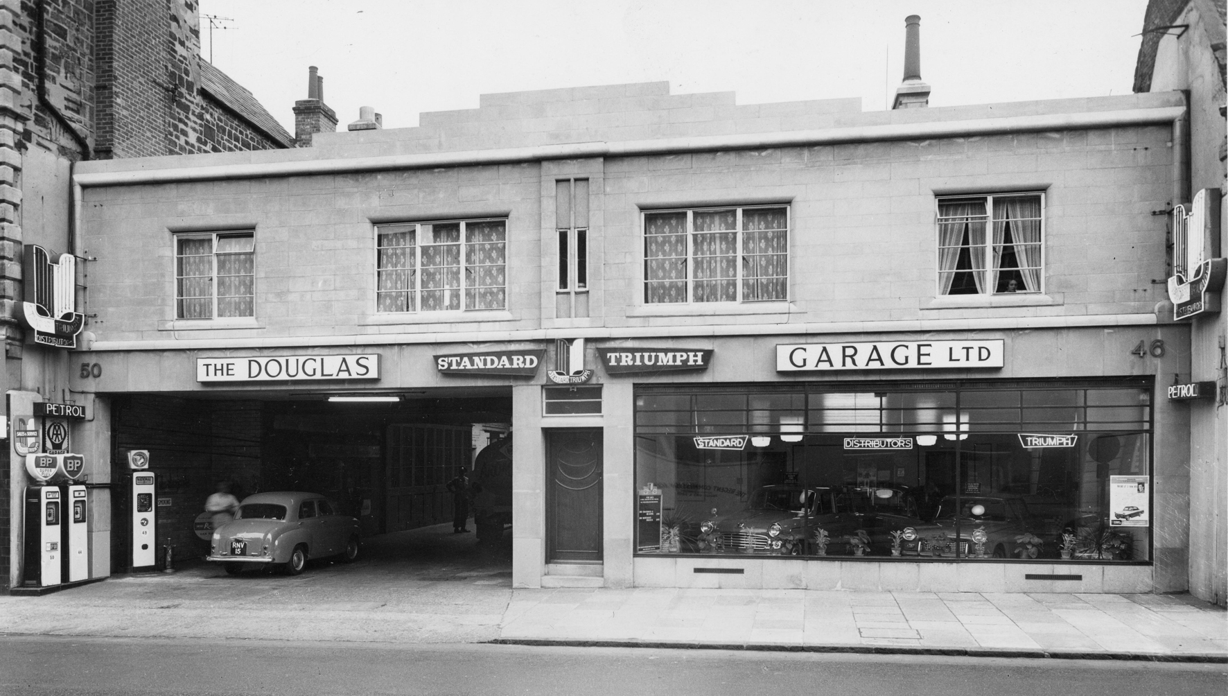 A photo of a car garage. There is an open garage door for cars to enter on the left, and a glass showroom window on the right. Fuel pumps can be seen on the far left, and there is a second story above the garage. The building is elegant and features art deco ornamentation.