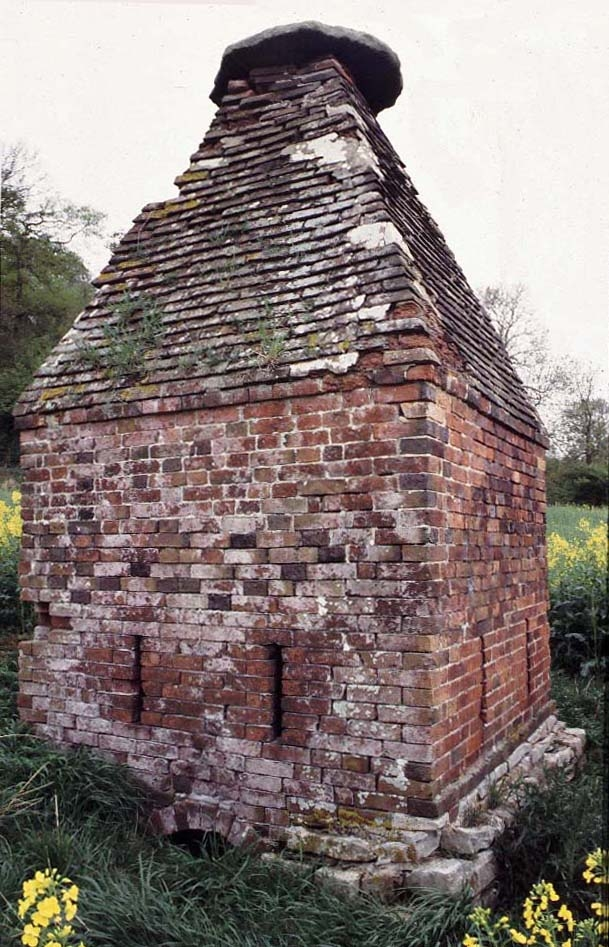 A photo of a small, square red-brick building with a steep, triangular brick roof. A stone foundation is visible, as is a stone cap at the apex of the roof. The building is surrounded by grass and yellow flowers.
