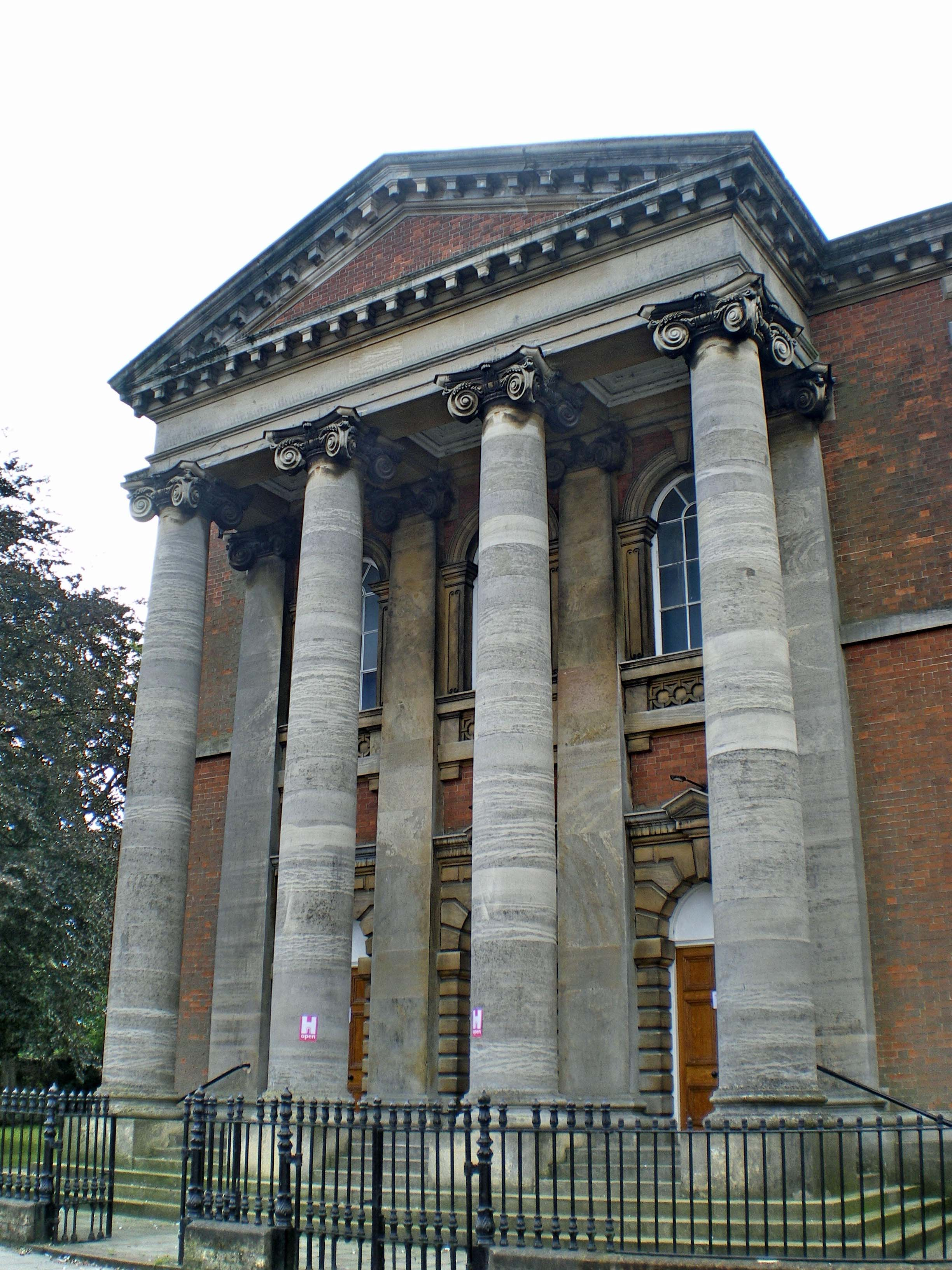A photo of a the front of a large red brick building, showing two ranks of four very tall stone columns supporting a pediment.