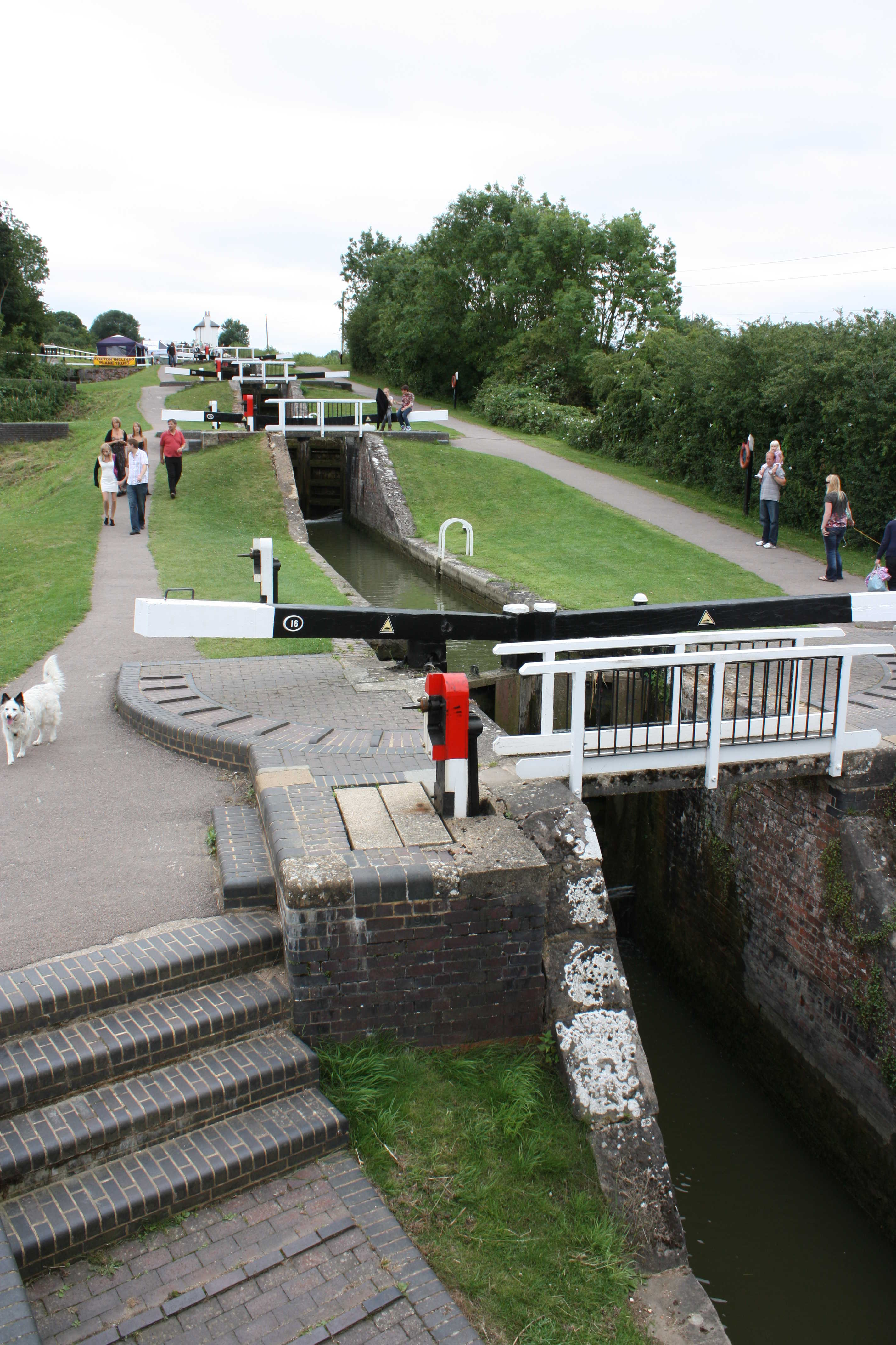 A photo of a long chain of locks on a narrow canal. People are walking along paths on both sides, and the locks are smartly painted in black, white and red.