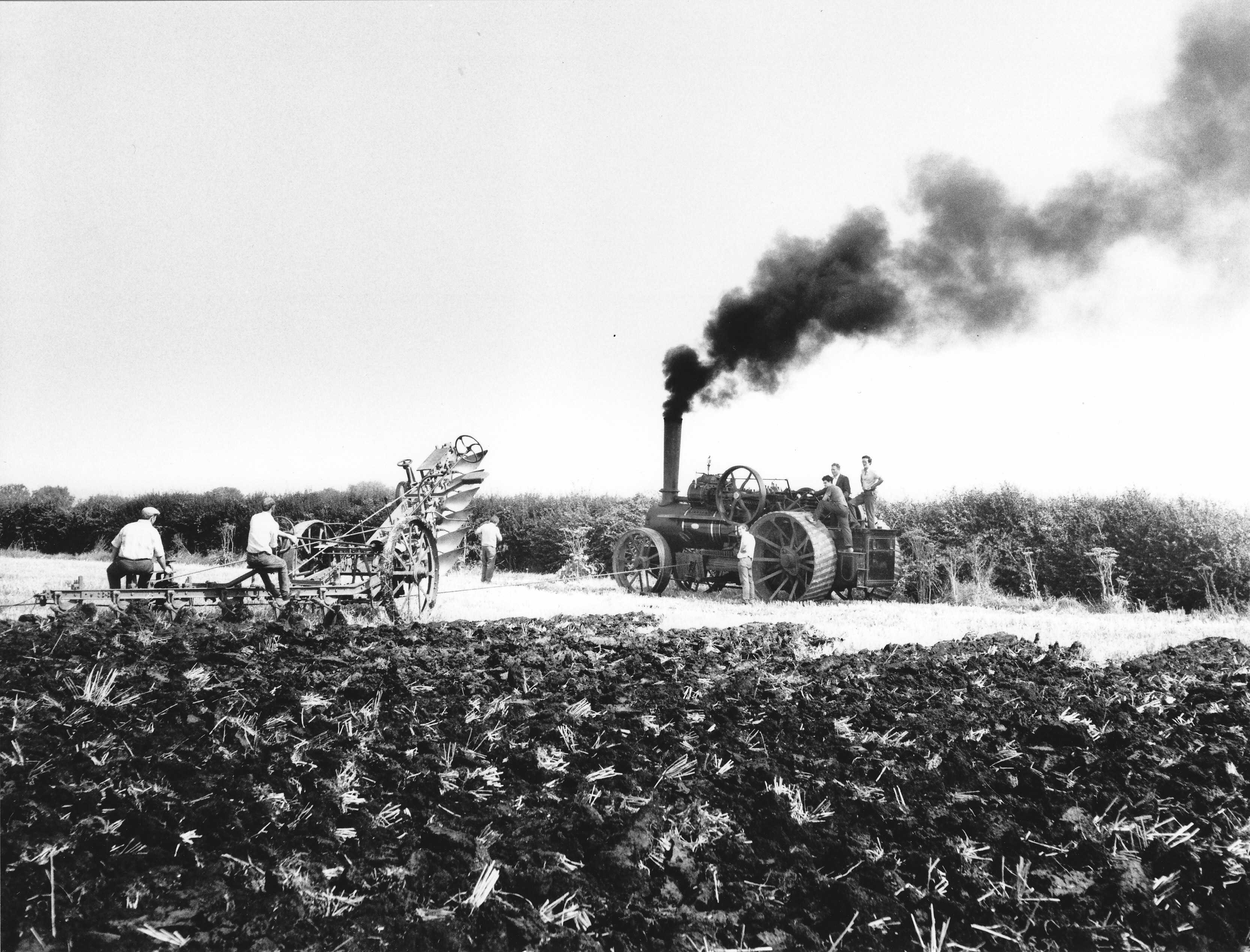 A black and white photo of a plough being pulled across a field by a rope attached to a traction engine. Black smoke can be seen coming from the engine's chimney. Two men ride the plough, while four more stand on the engine.