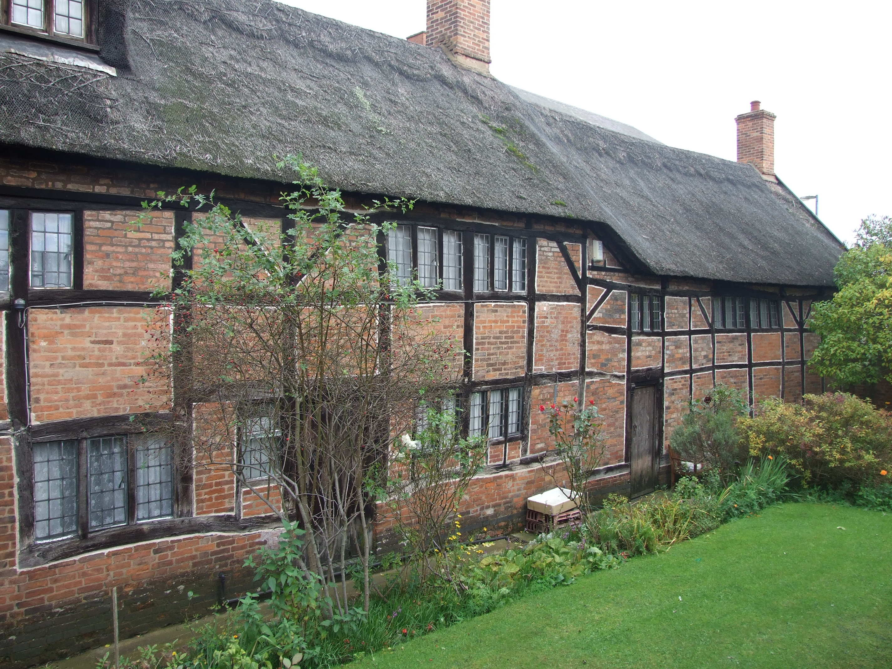 A photo of a three story brick building, with a wooden frame inlaid in the brickwork and a thatched roof. There are many windows, each containing lots of small panes of glass. In front of the building is a garden and lawn.