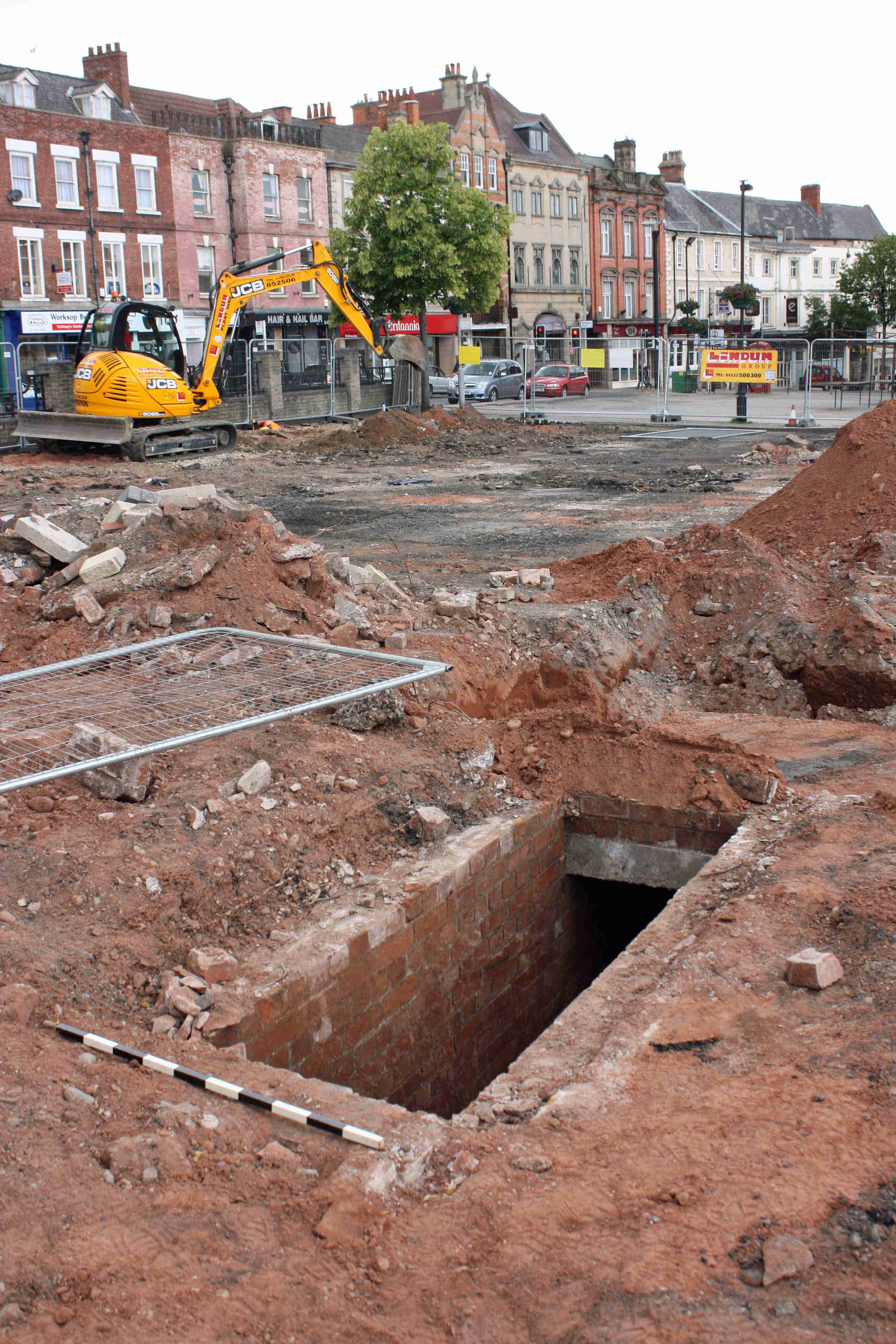 A photo of a building site in a town square. In the foreground, a hole in the ground leads to a buried, brick structure.