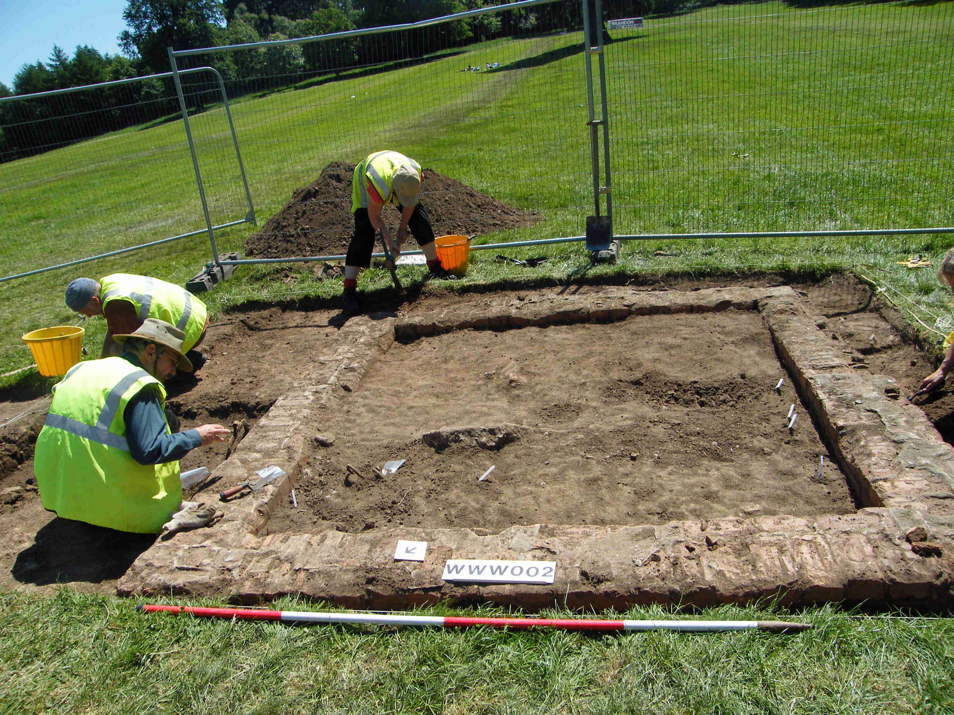 A photo of three archaeologists excavating on a small square stone foundation in a green field. The structure is approximately four metres across, and the walls are approximately half a metre thick.