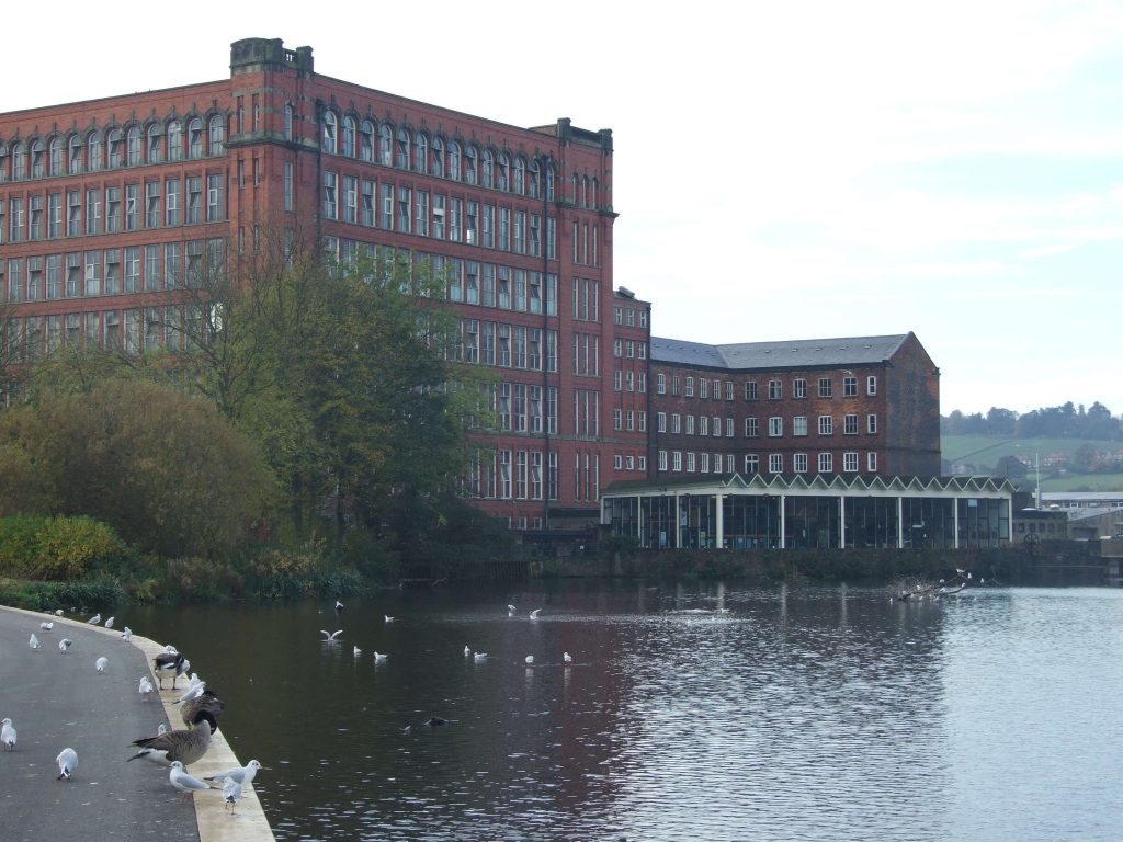 A photo of a very large, six story red brick building, standing next to a large body of water.
