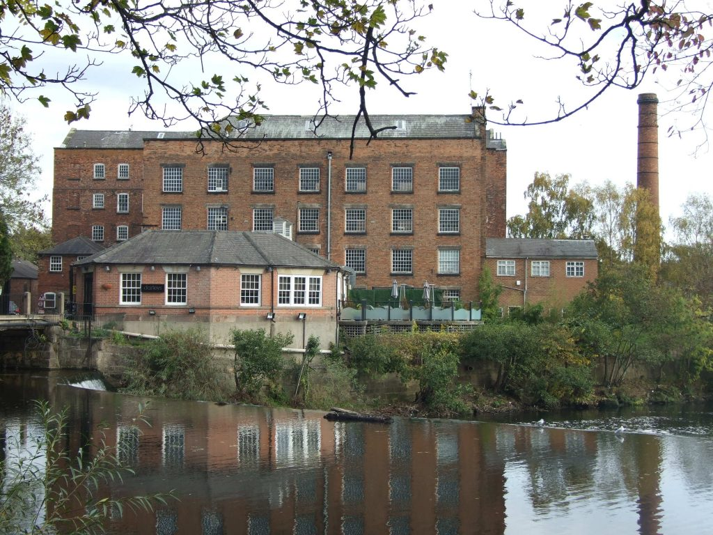A photo of a large brick building next to a river. The building has a large chimney and is surrounded by smaller buildings.
