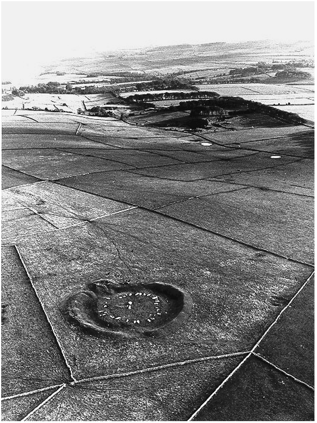 An aerial photo showing a large circular earthwork amongst fields. There is a ring of stones in the centre of the earthwork. In the distance hills and woodlands can be seen.