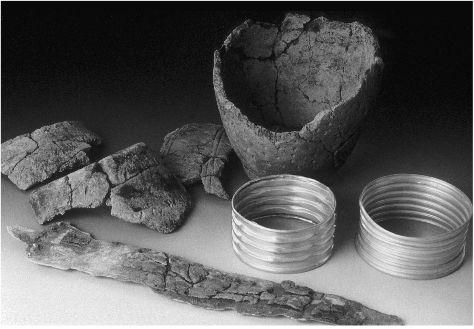 A photo showing a range of artifacts. Two ridged gold armlets appear in almost perfect condition, but all other items are badly worn and cracked. a dotted pattern can be made out on the surface of the pottery.