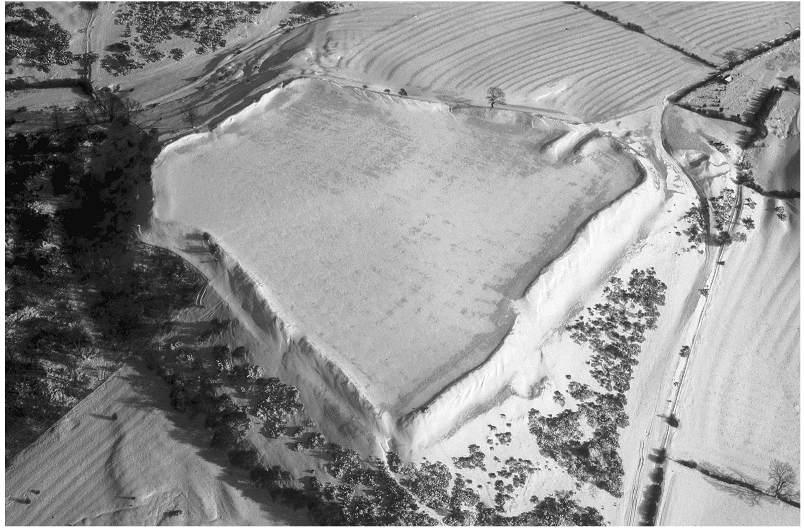 A black and white aerial photo of a large, roughly square hill fort. The edges of the fort are defined by tall ridges in the earth, outside of which are ditches. The inside of the square is relatively featureless.