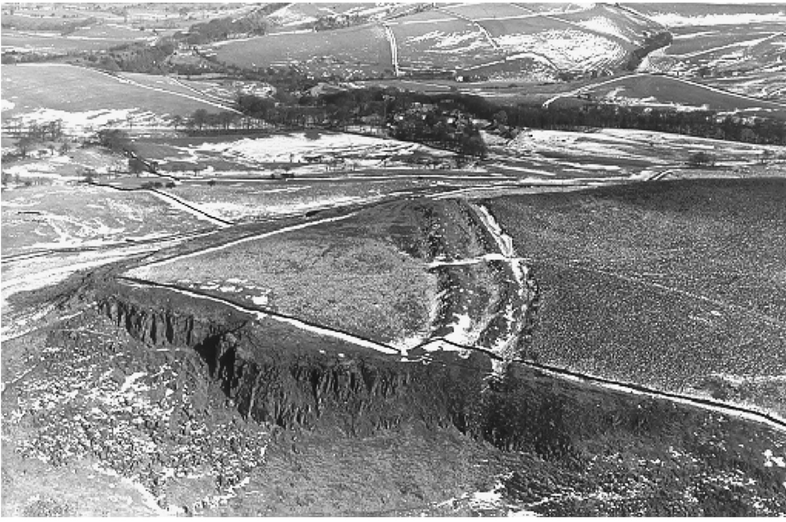 A black and white aerial photo showing a clifftop. There is an enclosed area formed by the cliff edge on one side and a large earthwork on the other. Fields and hills can be seen in the background.