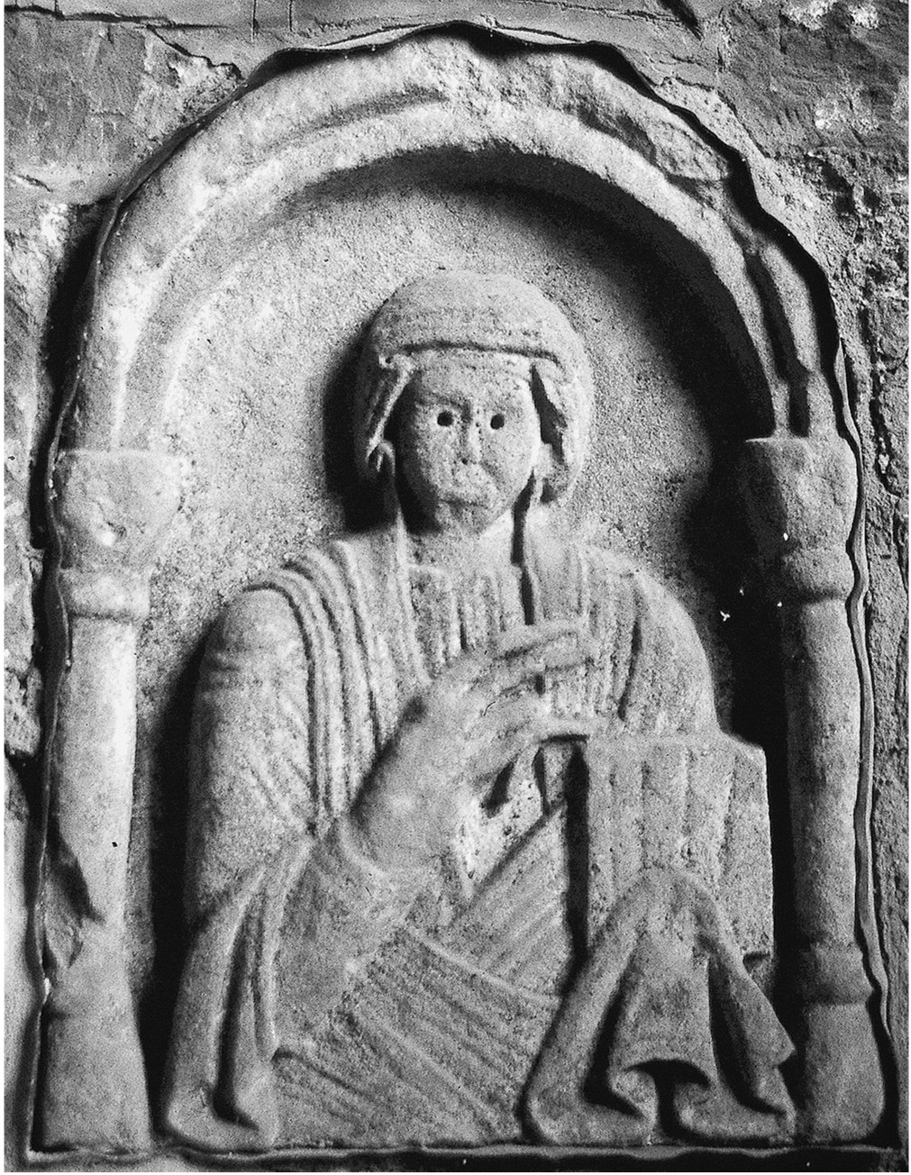 A black and white photograph of a carving of a person in a stone alcove. The figure is robed and holds an object, possibly tablet or book, in their left hand.