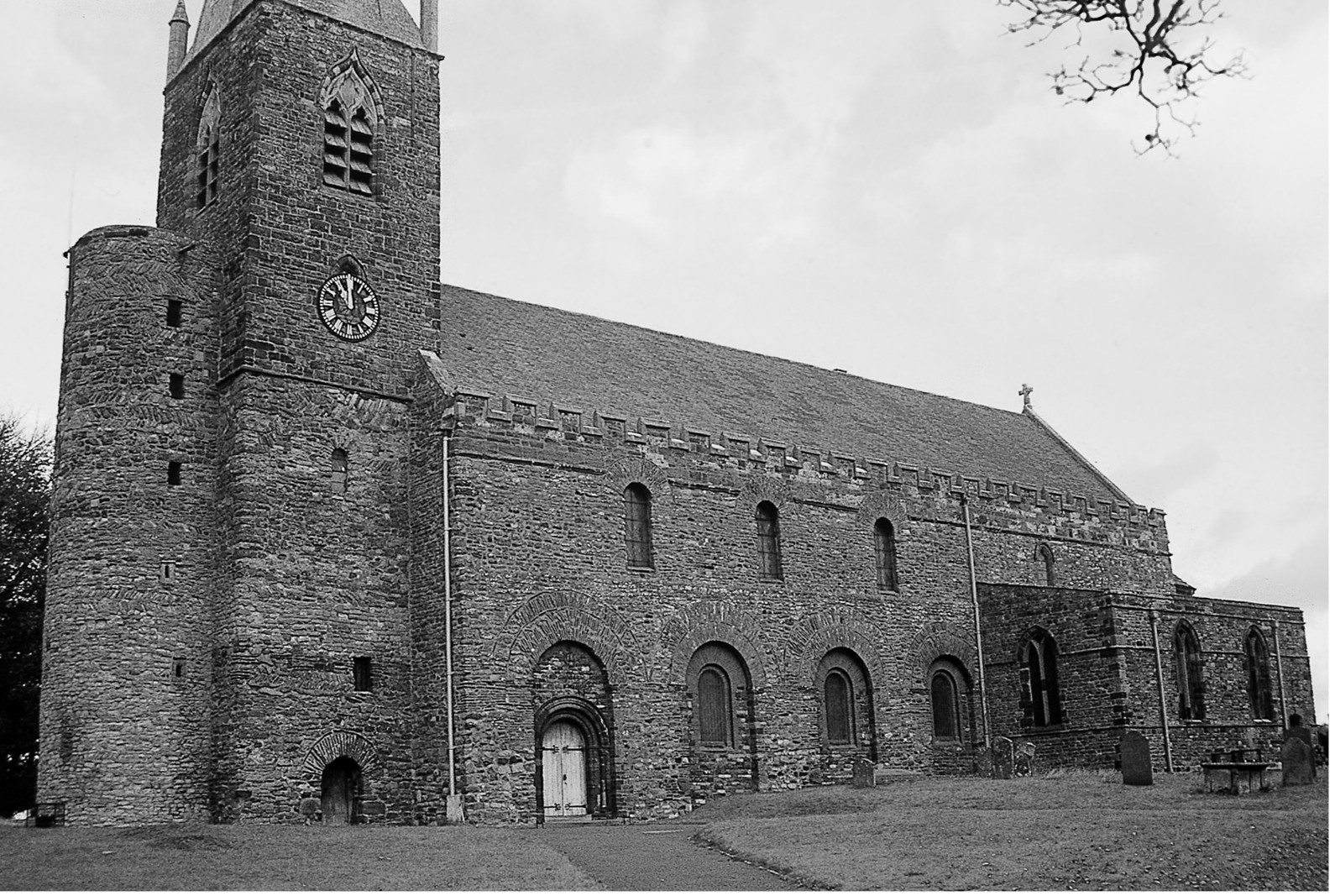 A black and white photograph of a church, constructed from  irregular stone blocks with small arched windows. There is a tower at the left hand end with a small clock on the side.