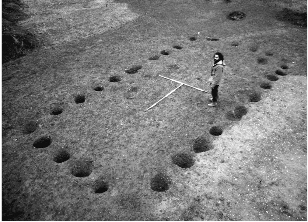 A black and white photograph showing an archaeological site from above. A rectangular shape is defined by rows of holes in the ground, measuring approximately 10 x 4 metres. A man stands for scale in the center.
