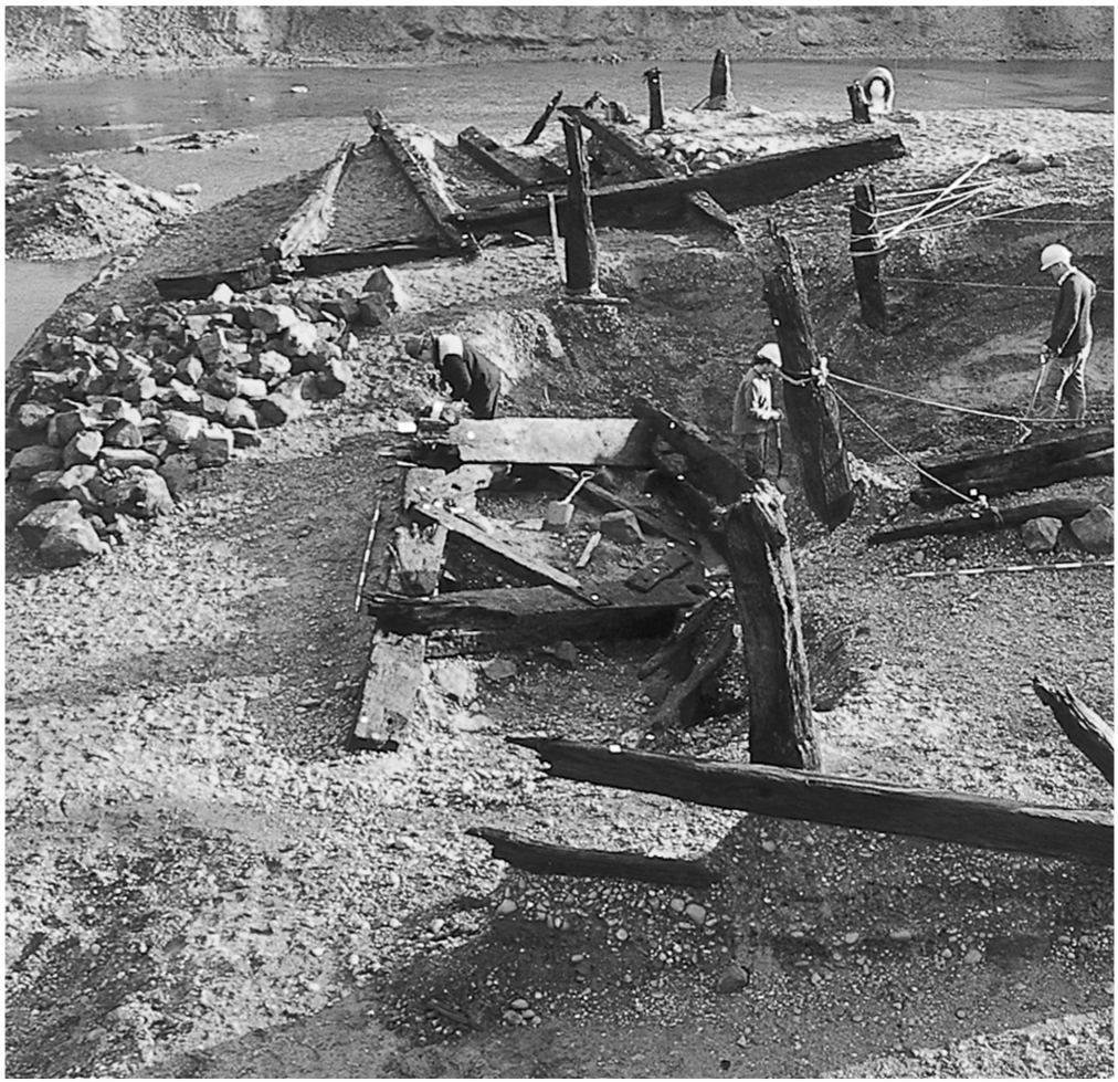 A black and white photograph of an archaeological site. In the background a river is visible. In the foreground large timber structures are being excavated.