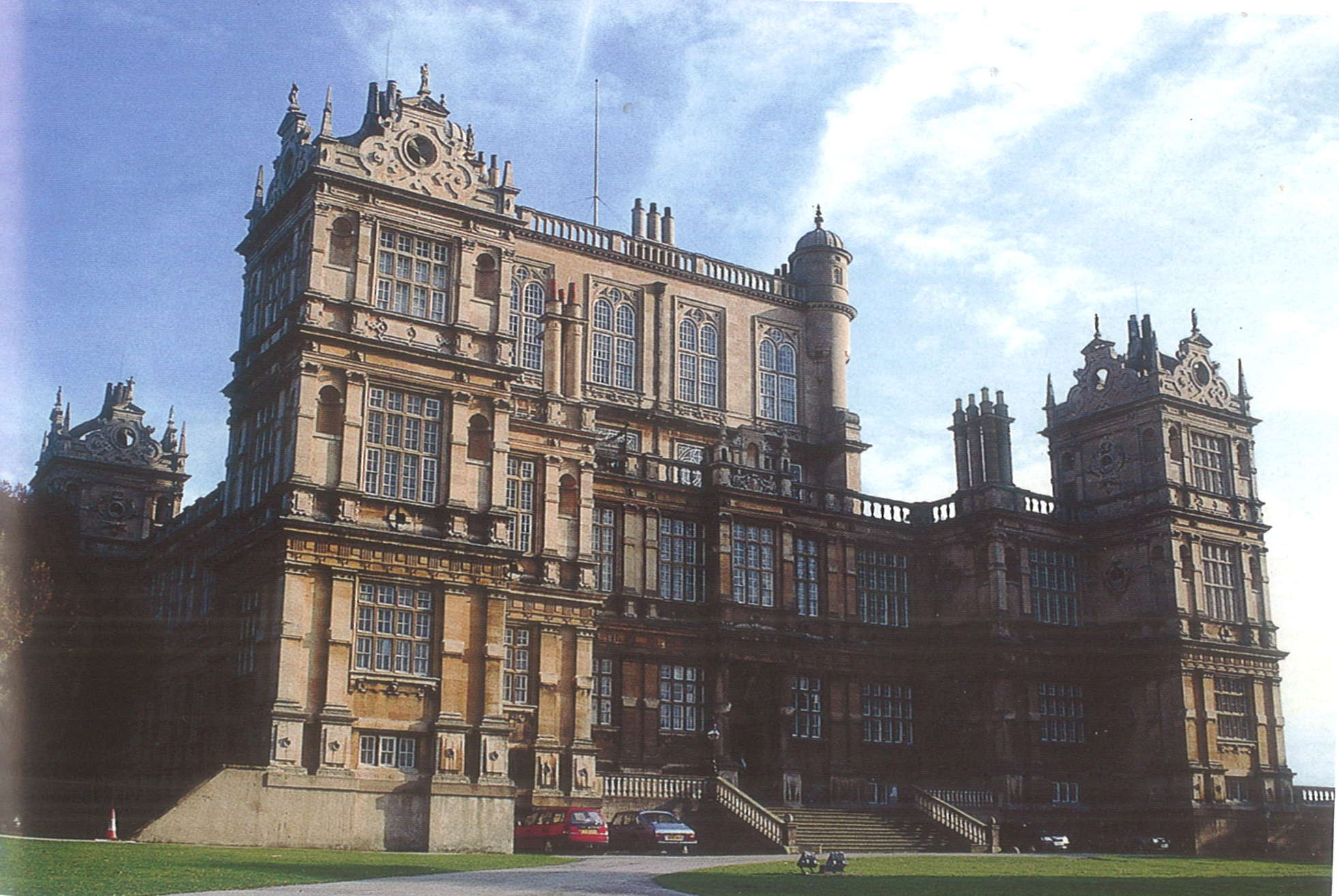 A photograph of the front of an extremely large and richly detailed manor house. Cars are parked beside a wide staircase leading to the front entrance, which is flanked by two large towers. A third tower can be seen further back on the structure. There are a great number of large windows.