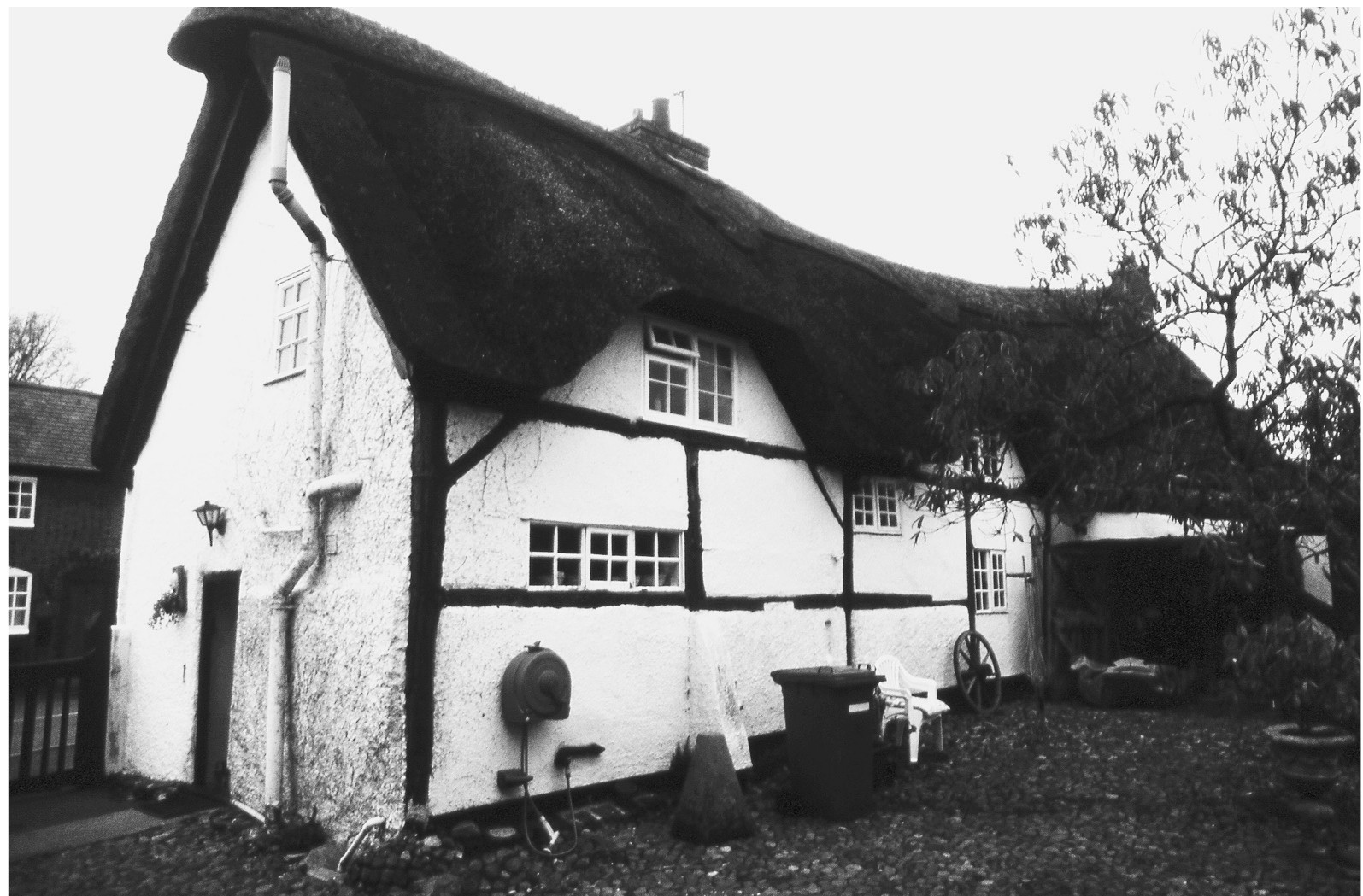 A black and white photograph of a building with a timber frame and thatched roof. The building has small, irregularly placed rectangular windows.
