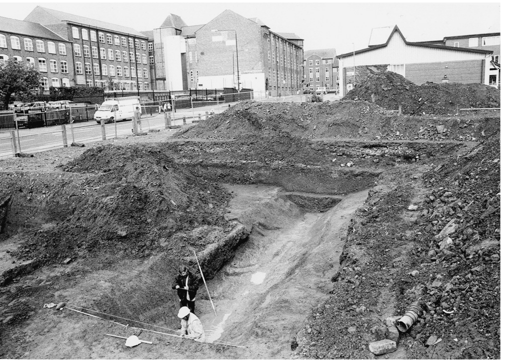 A black and white photograph of a large excavation. Two people work amongst large mounds of earth and debris. In the background can be seen buildings and streets.