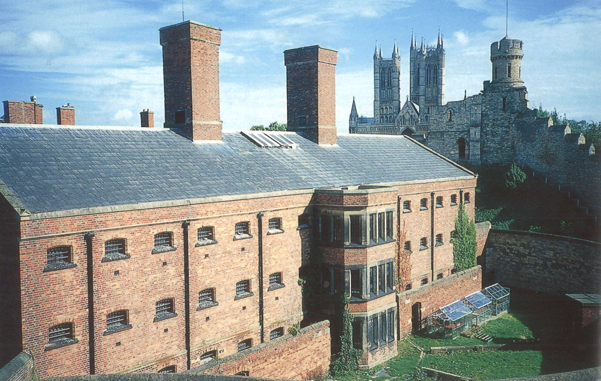 A photograph showing a large brick building in the foreground. The building has small, barred windows, a high wall, and two large chimneys. In the backgroudn can be seen Lincoln  Lincoln cathedral and the city walls.