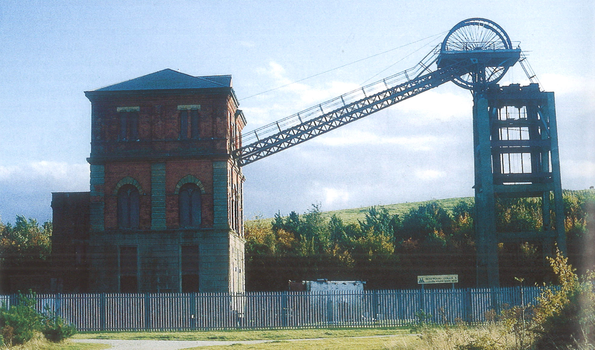 A photograph showing a brick tower on the left and a metal one on the right. The two are connected by a metal structure, and a large wheel can be seen at the top of the right-hand tower. The whole structure is surrounded by a metal fence.