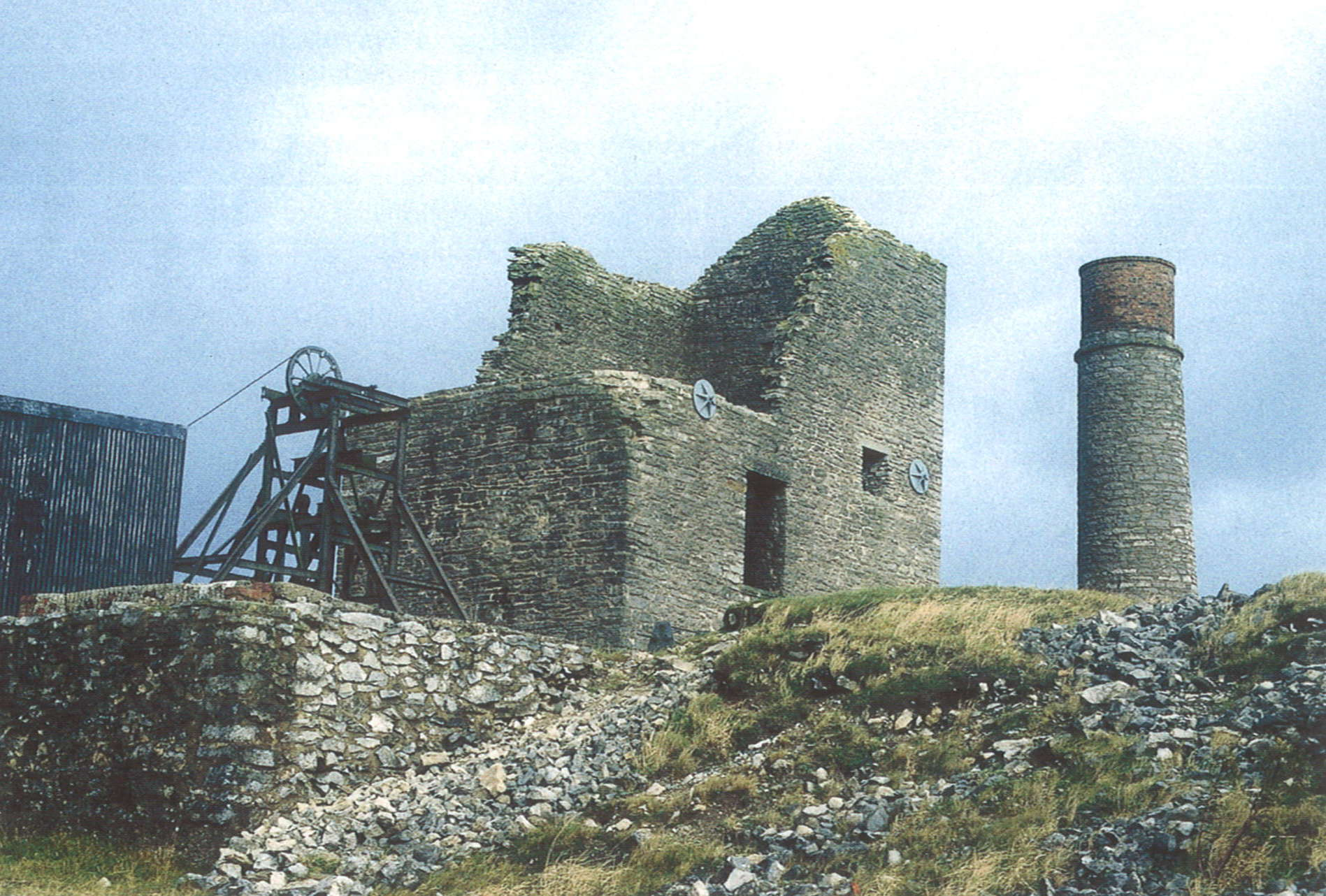 A photograph showing a ruined stone building and some wooden machinery. In the foreground is a grassy hillside strewn with rubble, and in the background can be seen a stone chimney.