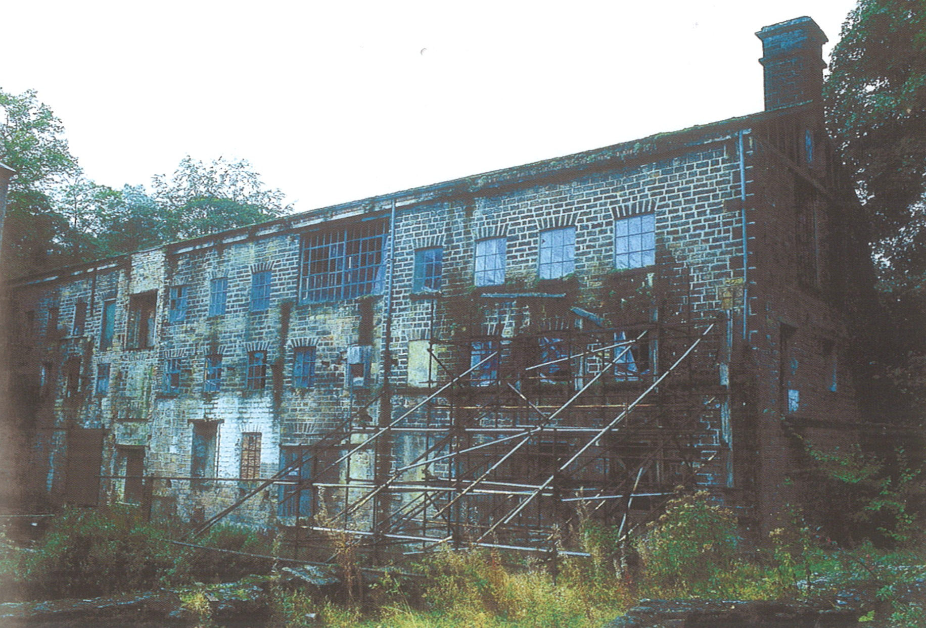 A photograph of a three story brick mill building. Scaffolding is supporting the right-hand front of the building, and overgrown foliage surrounds the base.