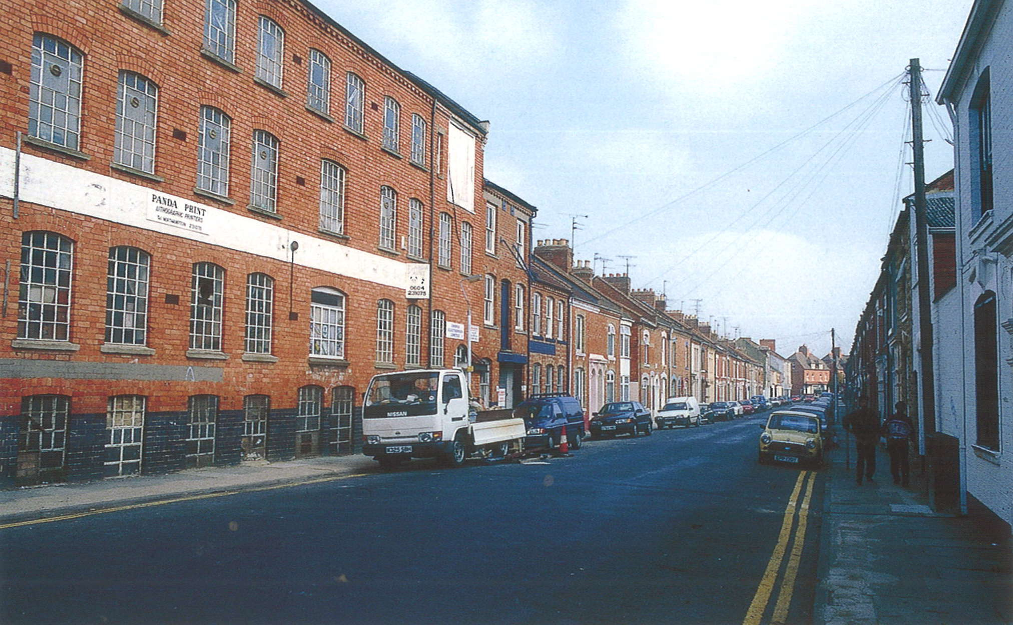 A photograph of a city street. Red-brick buildings line the left hand side, most notably a large four-story industrial building. Most of the other buildings appear to be houses.