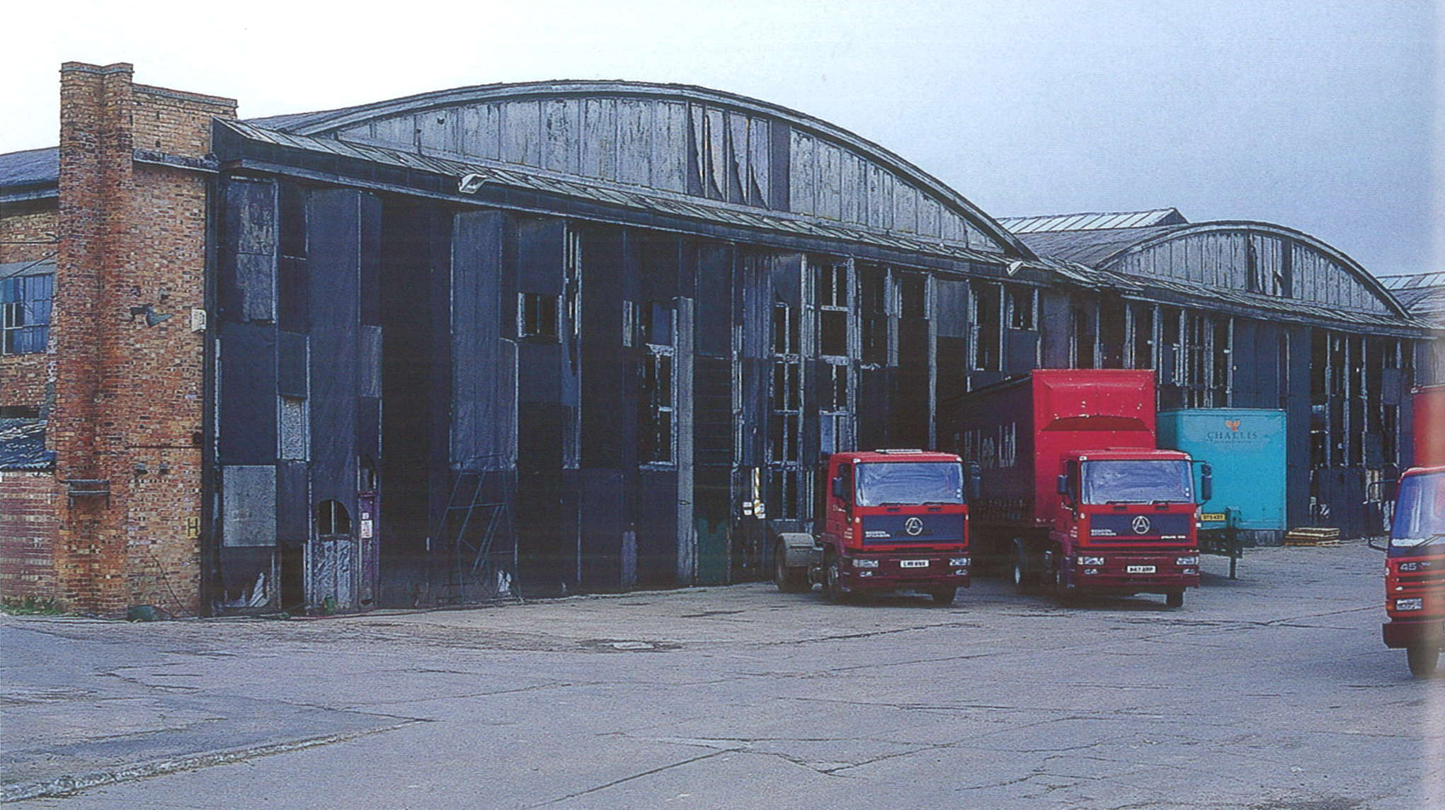 A photograph showing a very wide building, with brick walls and a metal roof divided into curved sections. Three red trucks are parked on a concrete apron in front of the building.