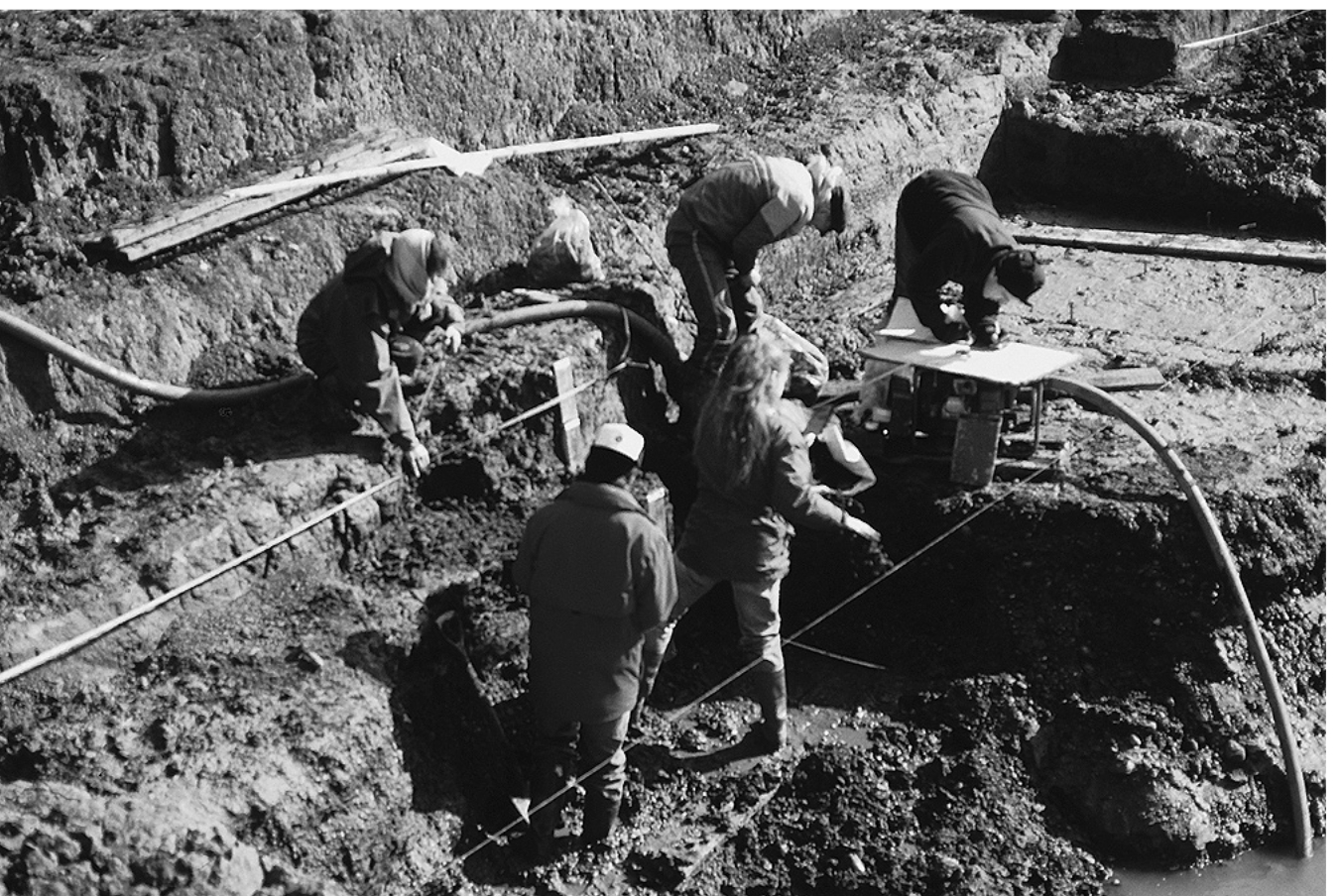 A black and white photograph showing several people working in an excavated trench. The lower layers are very muddy, and water is being pumped up from the bottom.