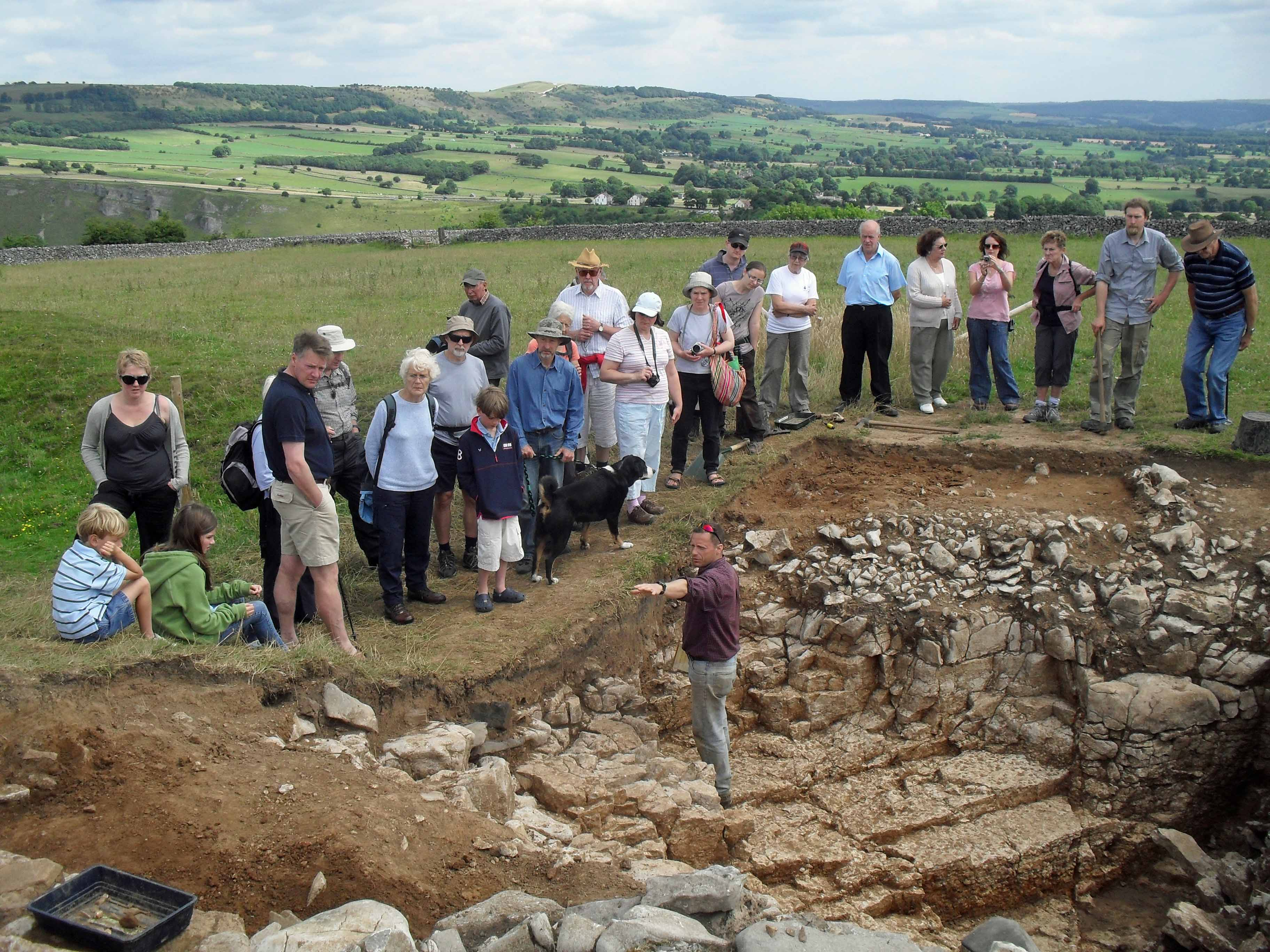 A photo of a group of people on a hillside, gathered around an archaeological excavation. In the pit can be seen complex rock formations, on which a man stands, addressing the group.