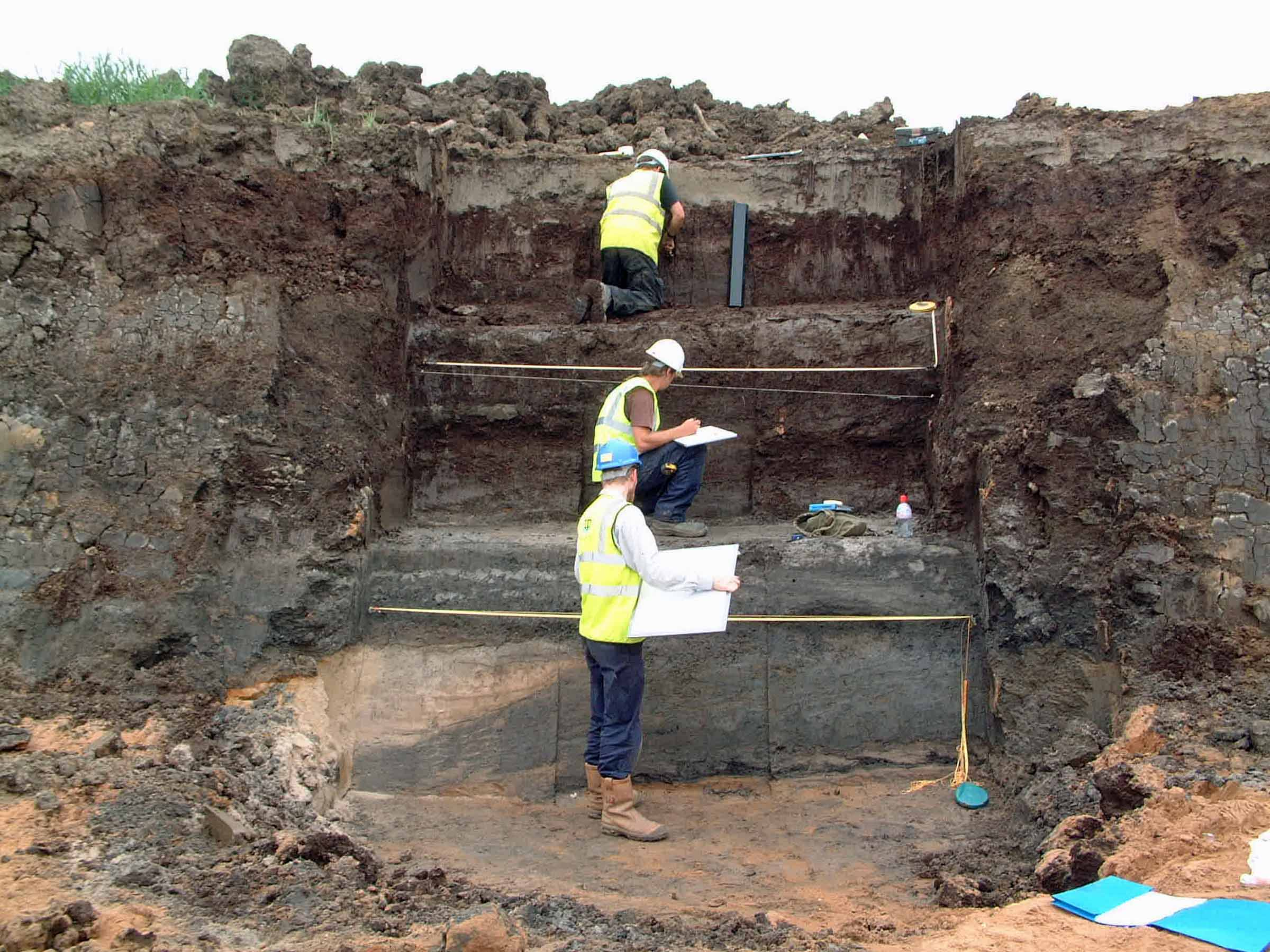 A photo of a deep archaeological excavation, showing three clear horizontal layers in an approximately 4-metre high vertical section. Three people in PPE are working at the face.