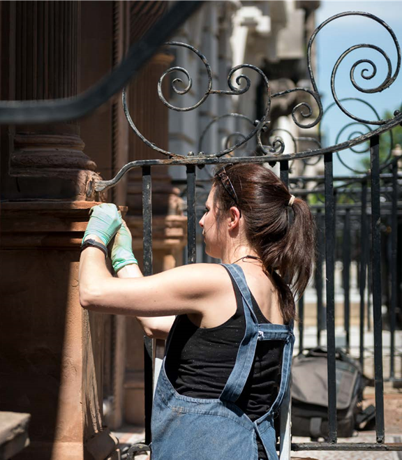 A woman undertaking conservation work on the entrance to a building on Harley Street, London
