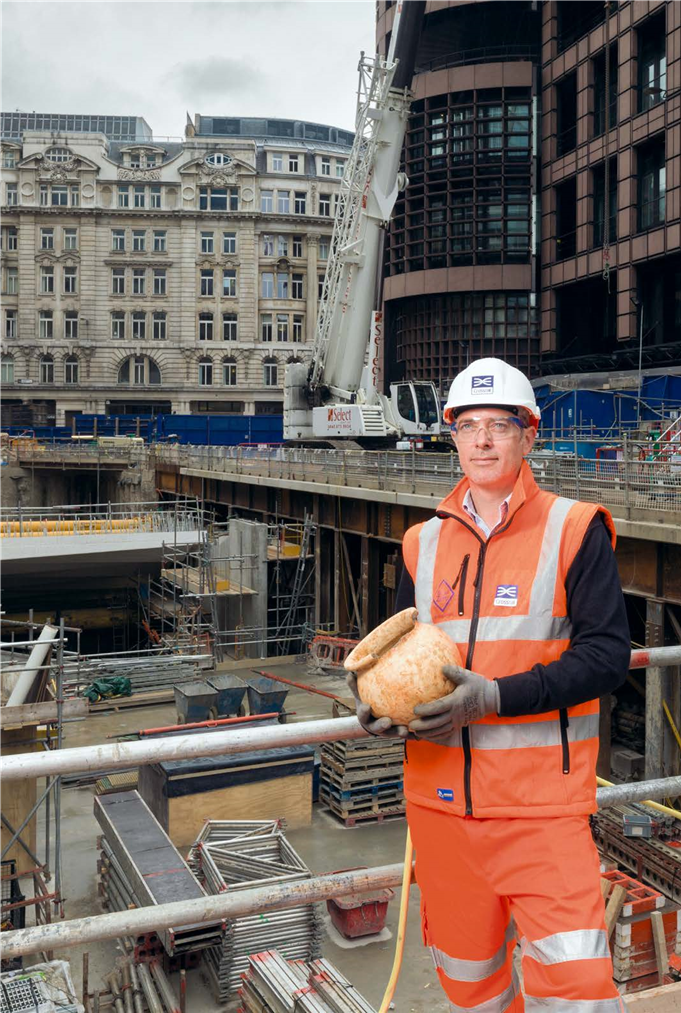 Photograph of the archaeologist Jay Carver holding a pot found during excavations of Crossrail in London