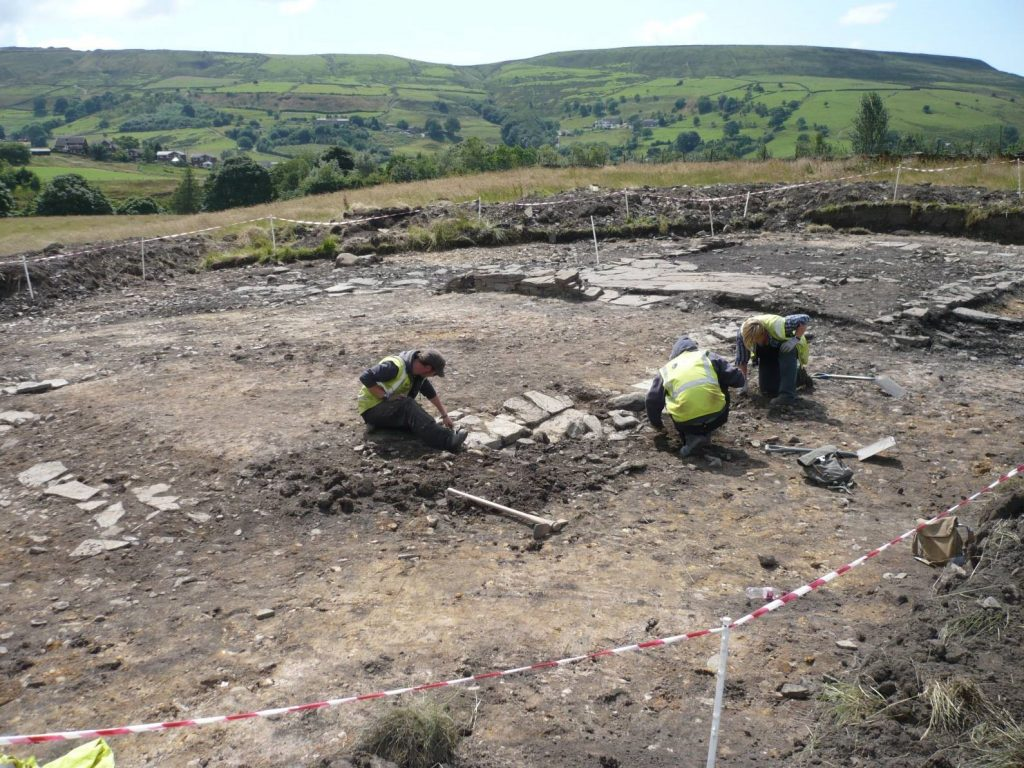 Photograph of three people excavated the stone remains of a barn