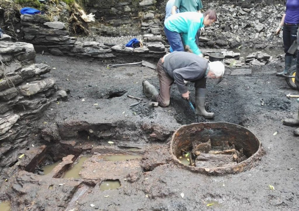 Photograph of people excavating remains on an archaeological site