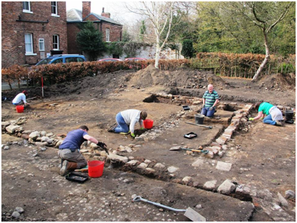 Photograph of people excavating the remains of a building