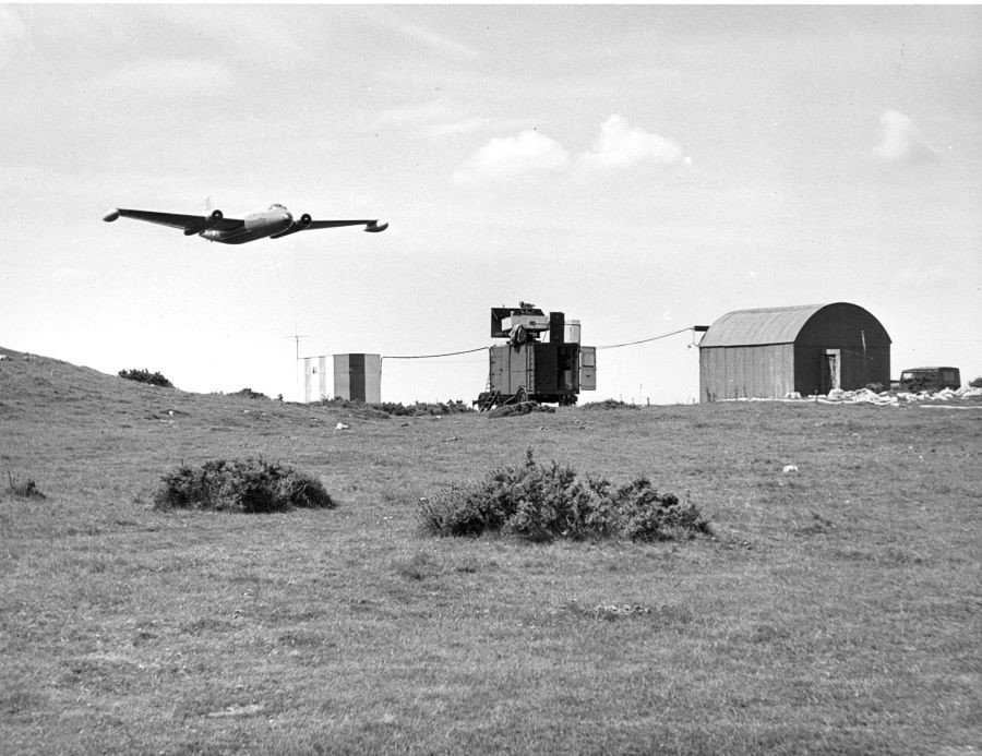 a photograph of an English Electric Canberra flying low over experimental radar equipment at Westbury Beacon, Somerset